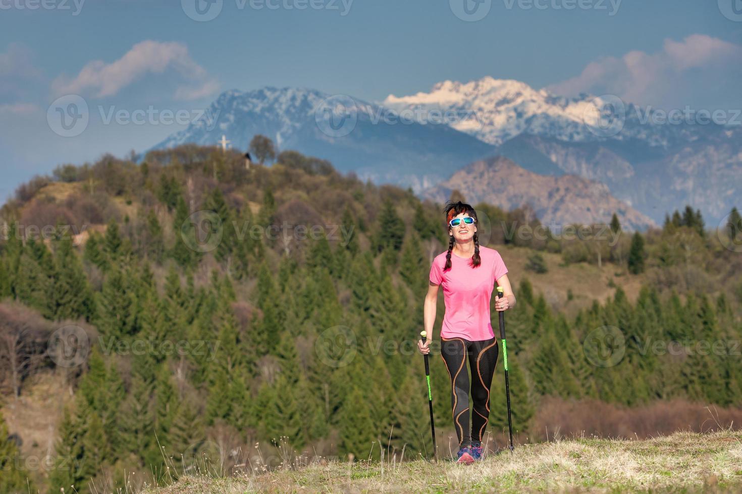 primavera en las montañas entre verde y nieve. una chica solitaria durante una caminata foto