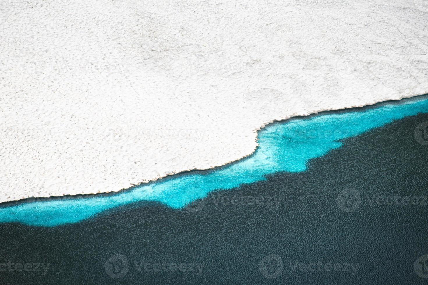 Línea de hielo y agua en un lago alpino en lo alto de las montañas foto