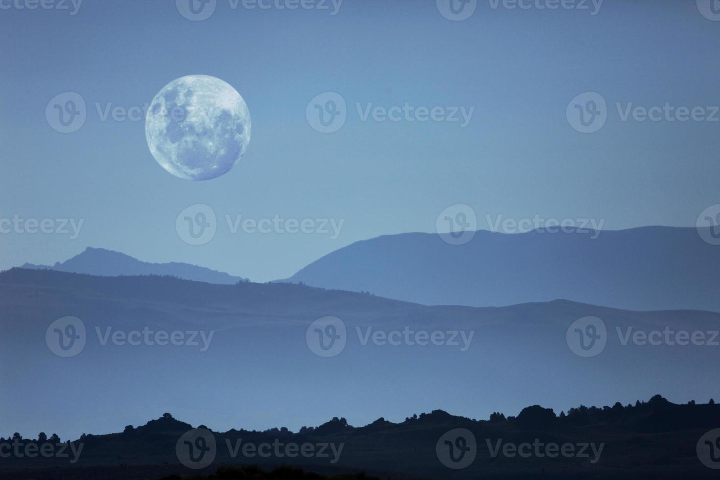 siluetas de montaña fantasmal y luna foto