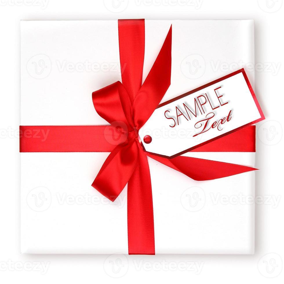 Bonito regalo navideño envuelto con cinta roja y etiqueta de regalo. foto