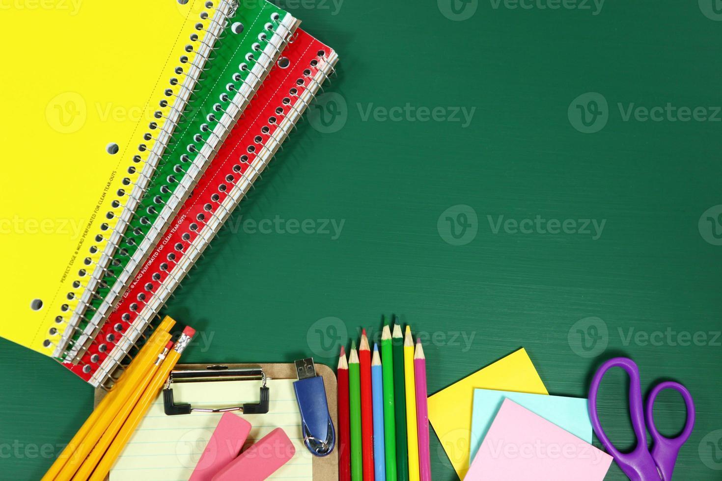 útiles escolares en pizarra en blanco foto