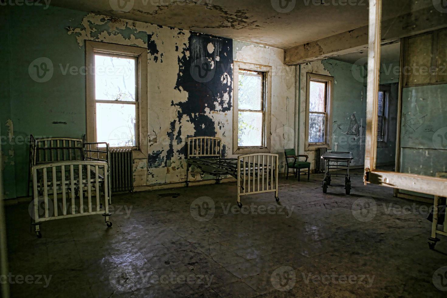 Edificio hospitalario derruido con camas oxidadas vacías foto