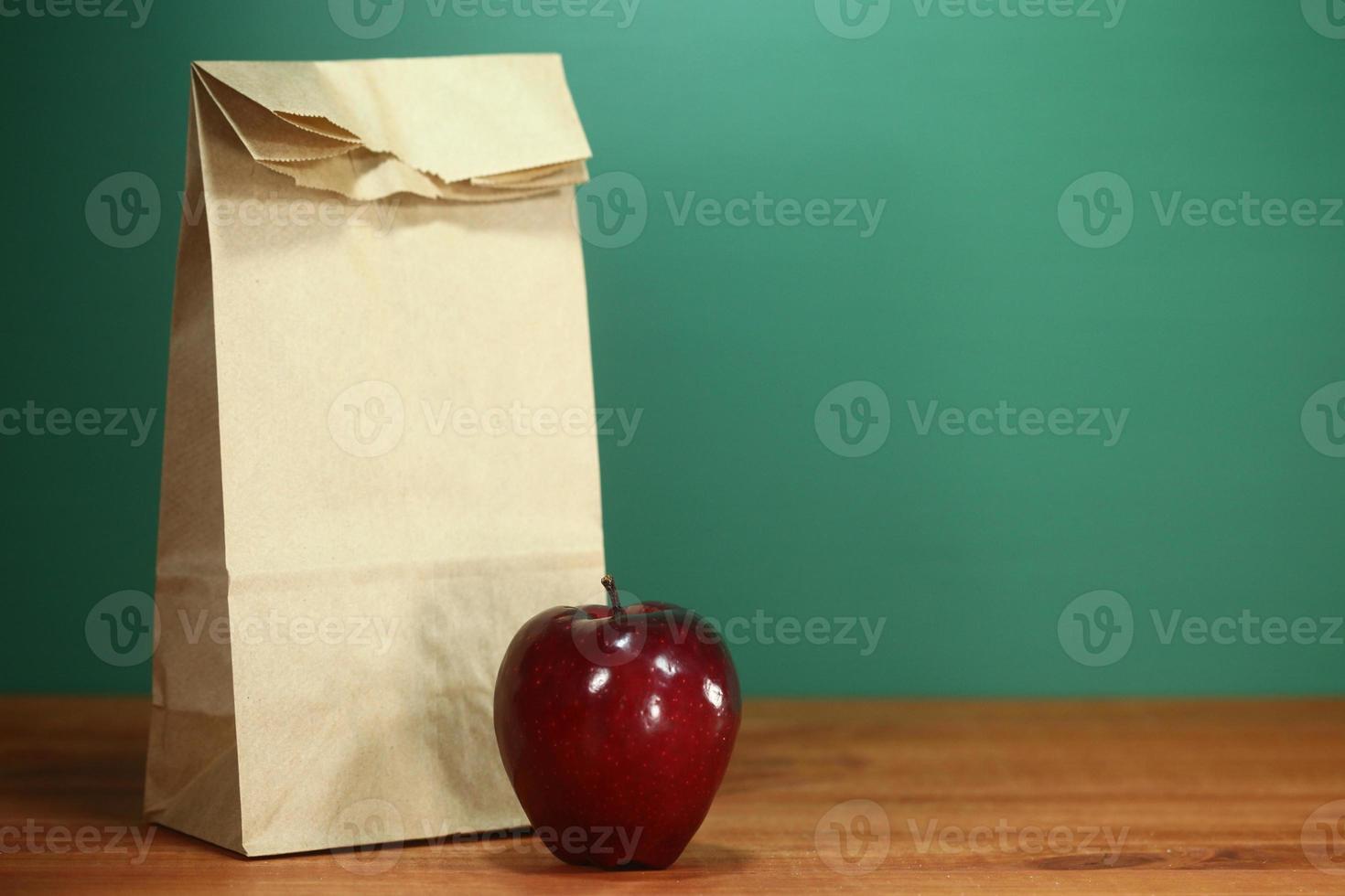 Saco de almuerzo escolar sentado en el escritorio del profesor foto