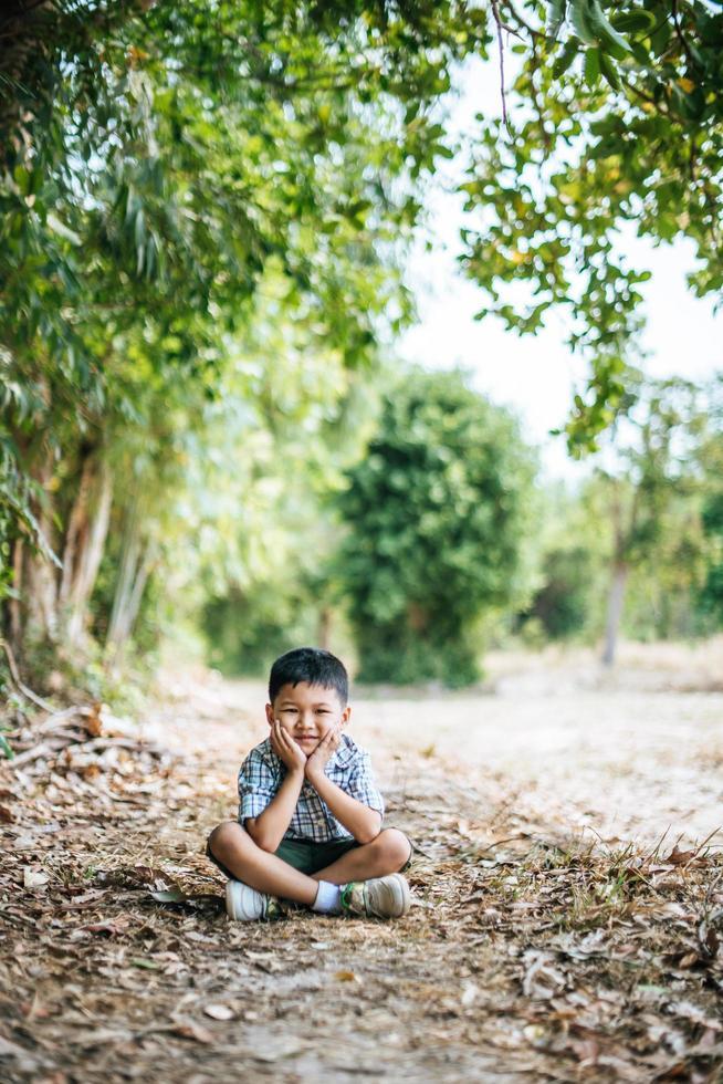 niño feliz sentado y pensando solo en el parque foto