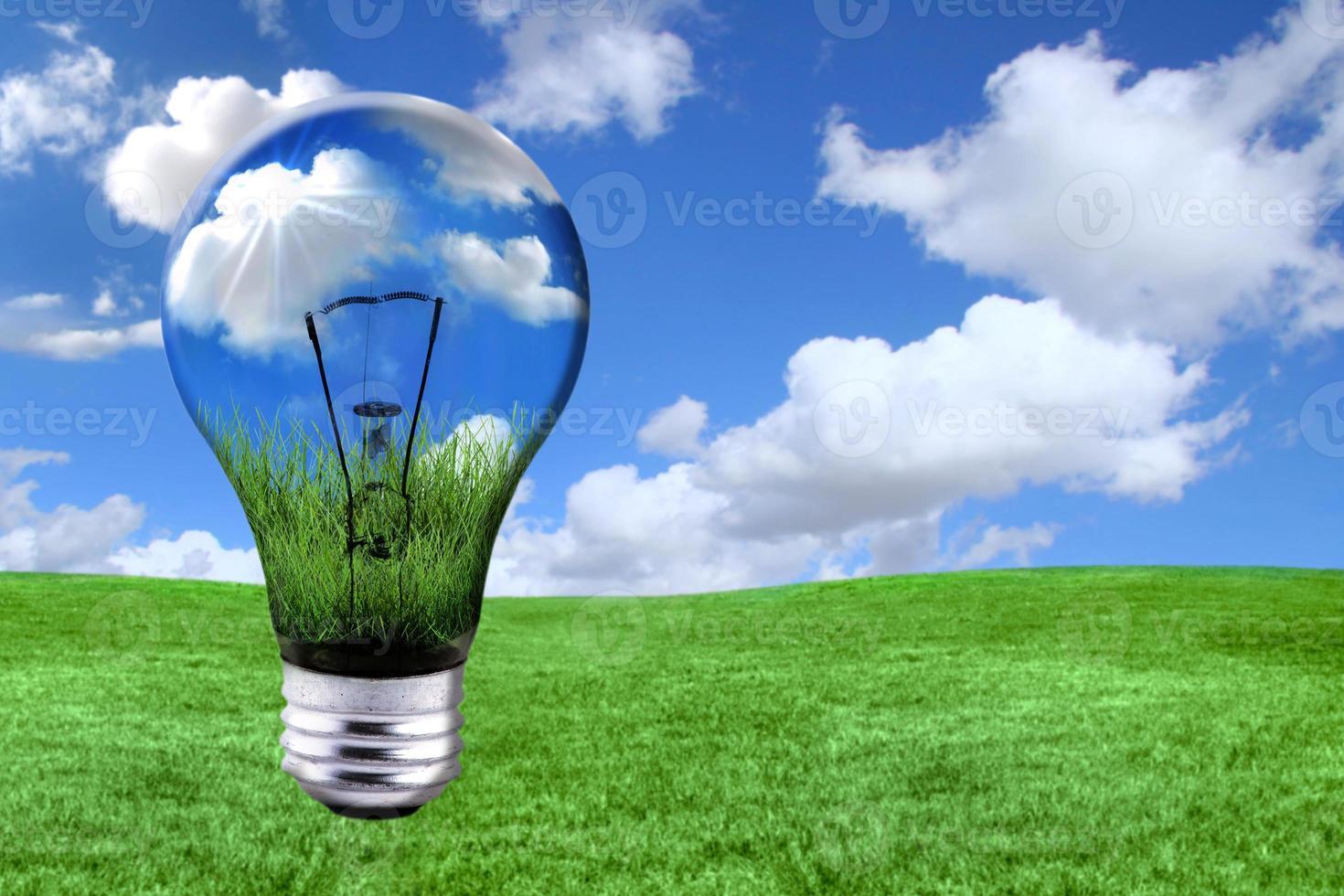 Soluciones de energía verde con bombilla transformada en paisaje. foto
