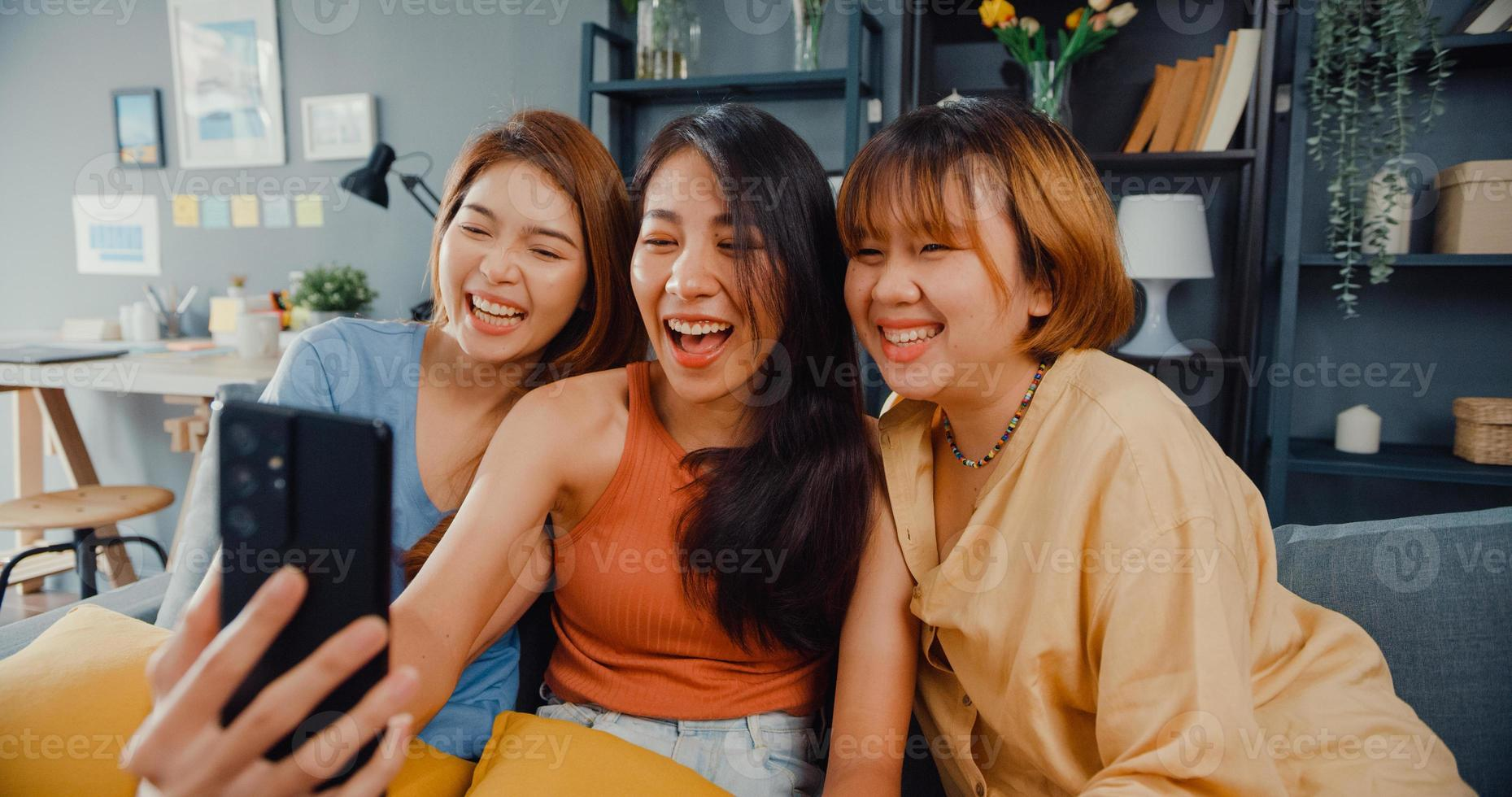 Group of teenager Asia women feeling happy smiling relax use smartphone video call in living room at home. Cheerful Roommate ladies video conference with friend, Lifestyle woman at home concept. photo