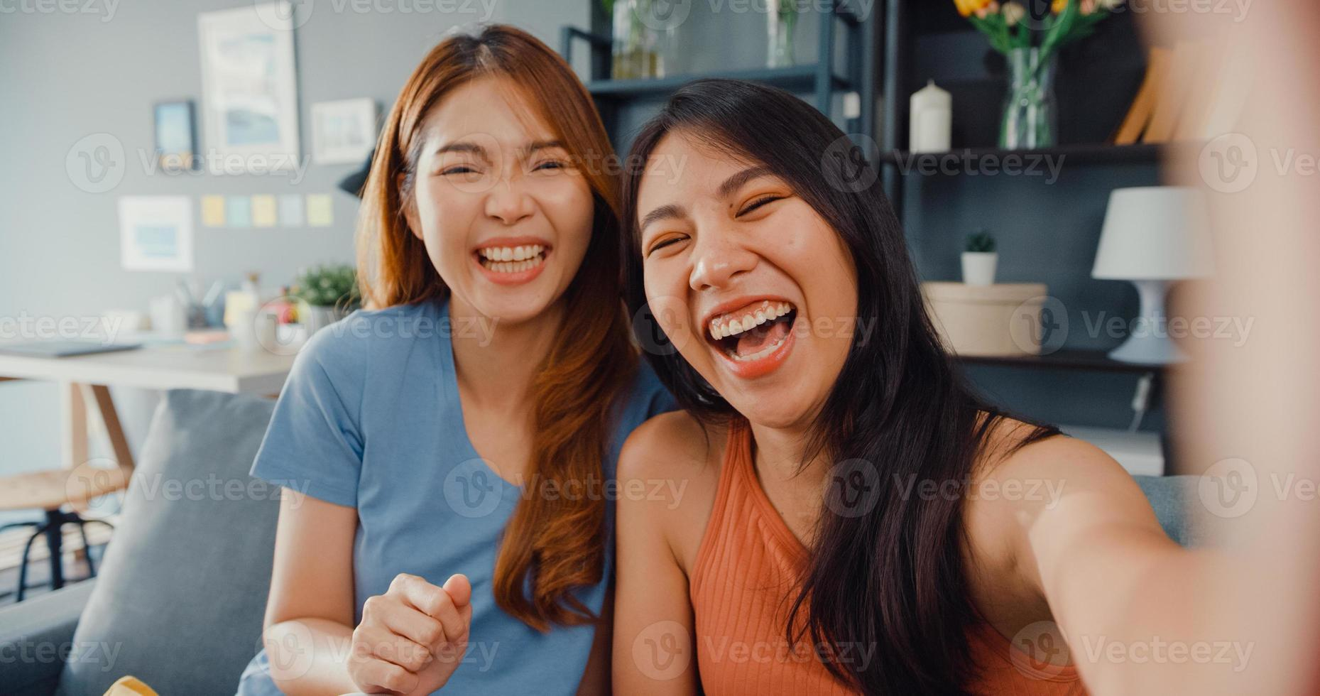 Teenager Asian women feeling happy smiling selfie and looking to camera while relax in living room at home. Cheerful Roommate ladies video call with friend and family, Lifestyle woman at home concept. photo