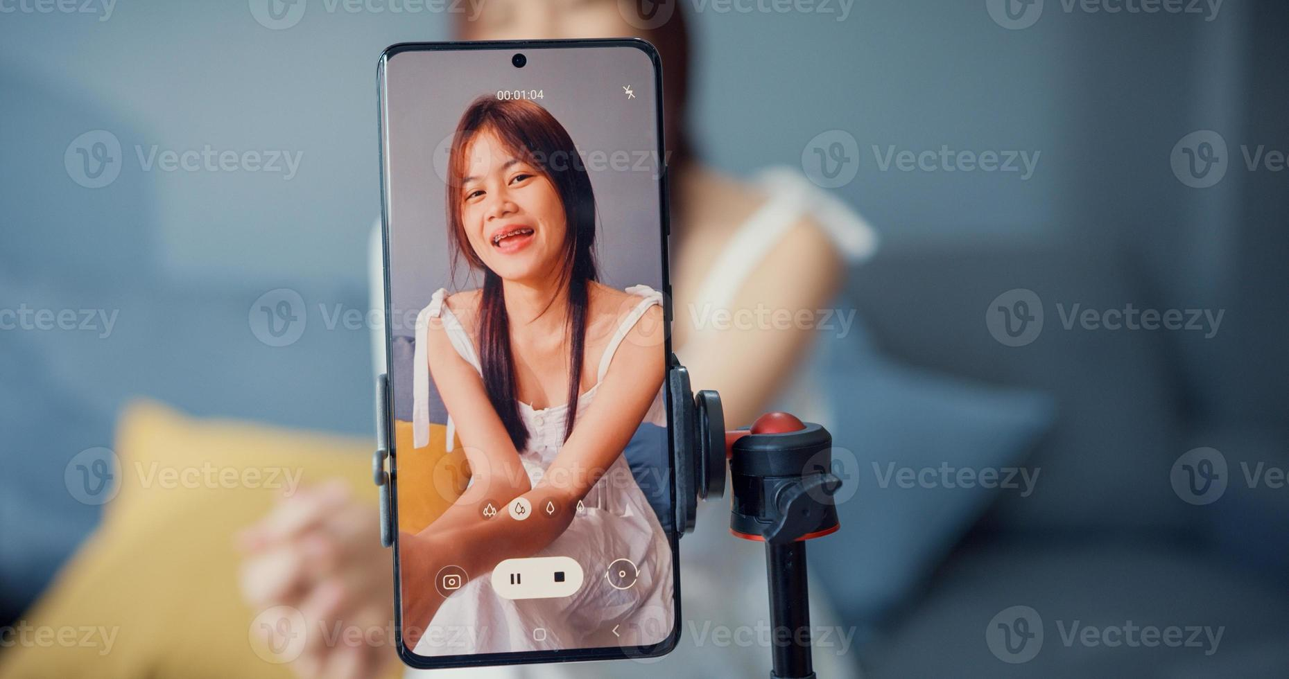 Happy young Asian girl blogger in front of phone camera use tablet enjoy question answer with follower in living room at home. Blogger activity lifestyle, Social distance coronavirus pandemic concept. photo