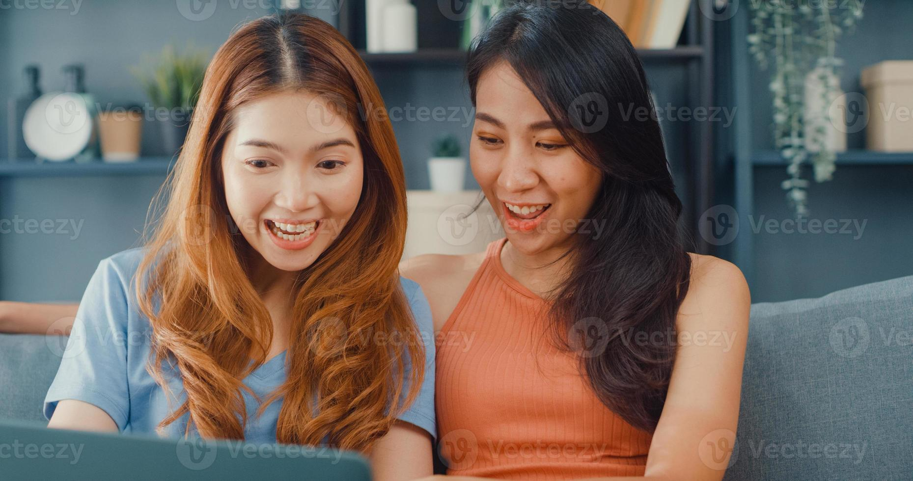 Two Asia lesbian women site on couch together looking at laptop screen in living room at home together. Happy couple roommate ladies enjoy web surfing online shopping, Lifestyle woman at home concept. photo