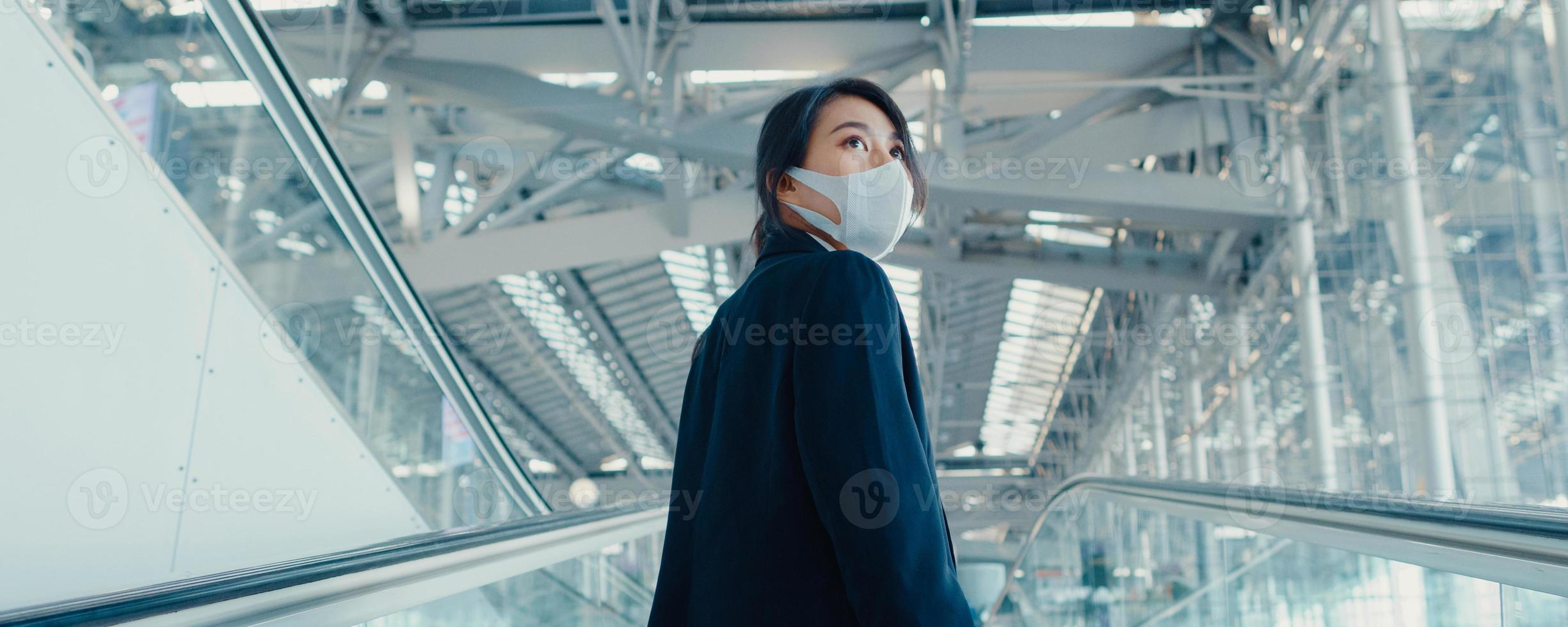 Asian business girl wear face mask drag luggage stand on escalator look around walk to terminal at international airport. Business travel social distancing concept. Panoramic banner background. photo