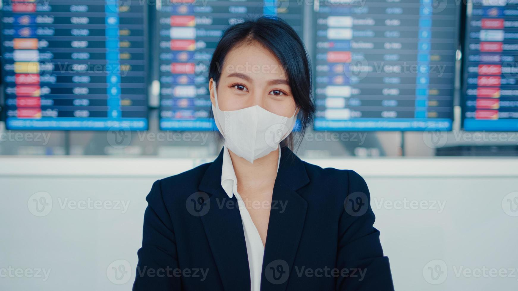 Asian business girl wear face mask stand in front of board flight show time look at camera international airport. Business commuter covid pandemic, Commuter social distancing, Business travel concept. photo