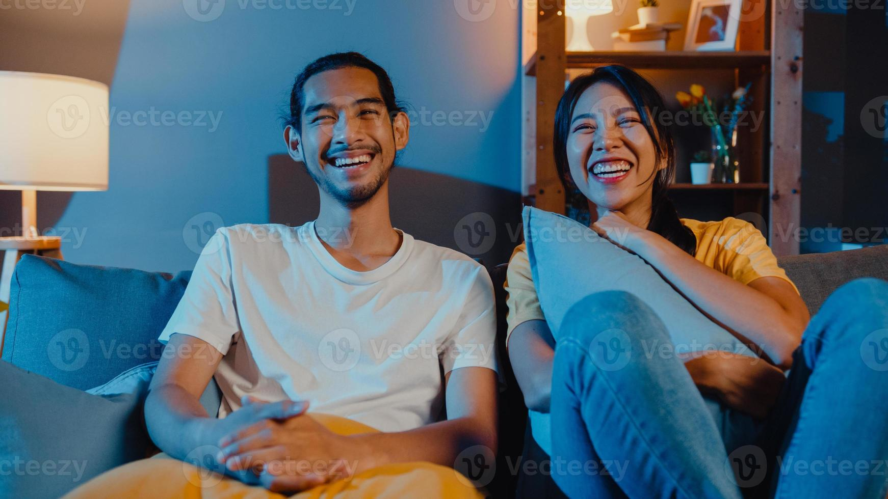 Romantic asia couple man and woman smile and laugh lay down on sofa in living room at night watch comedy movie on television together at home. Married couple family lifestyle, stay at home concept. photo
