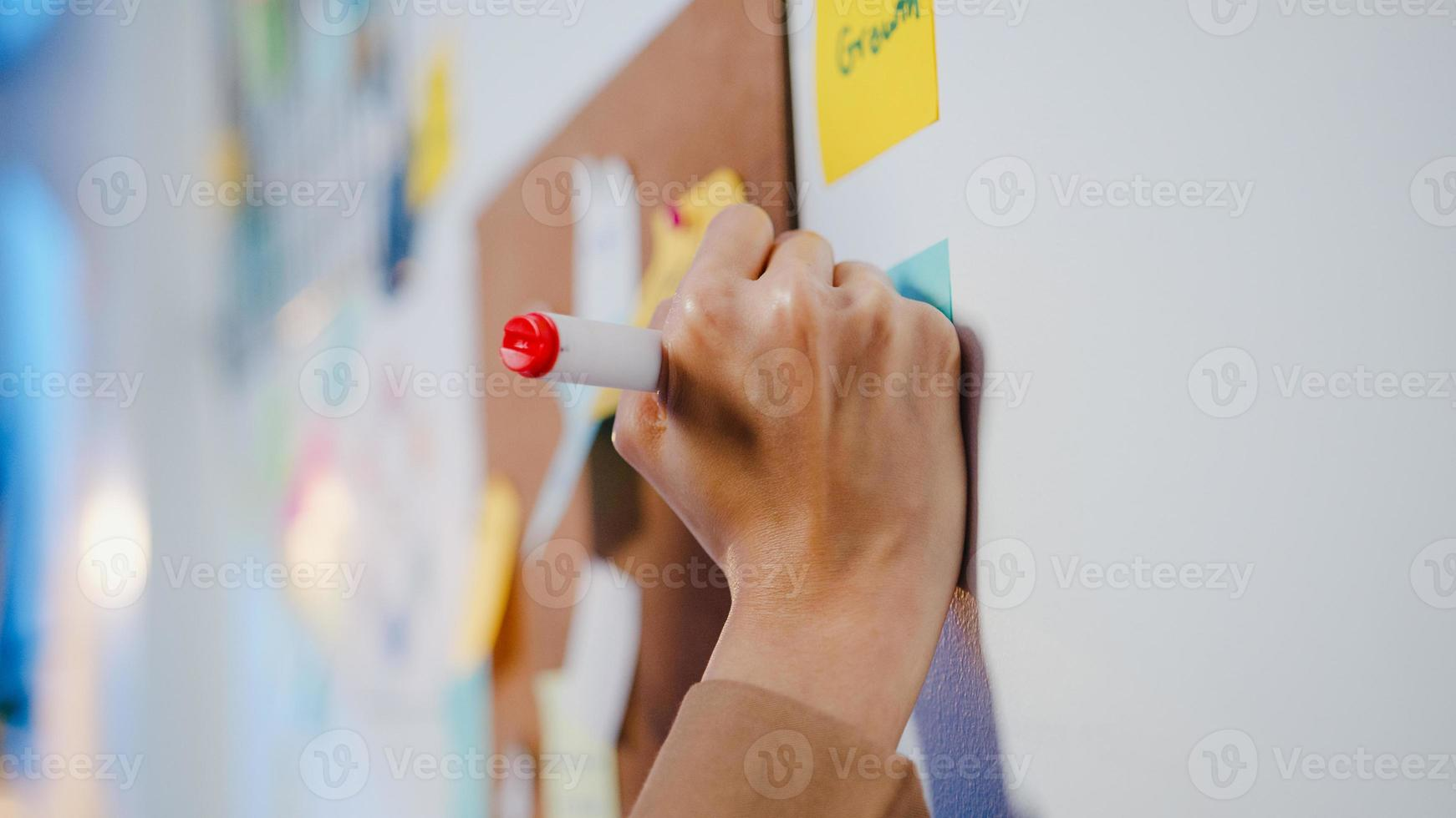 Group of young Asia businesspeople discussing business brainstorming meeting working together sharing data and writing whiteboard on wall with sticky note in night office. Coworker teamwork concept. photo