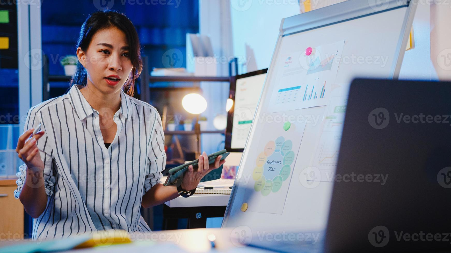 Asia businesswoman social distancing in new normal for virus prevention looking at camera presentation to colleague about plan in video call while work in office night. Lifestyle after coronavirus. photo