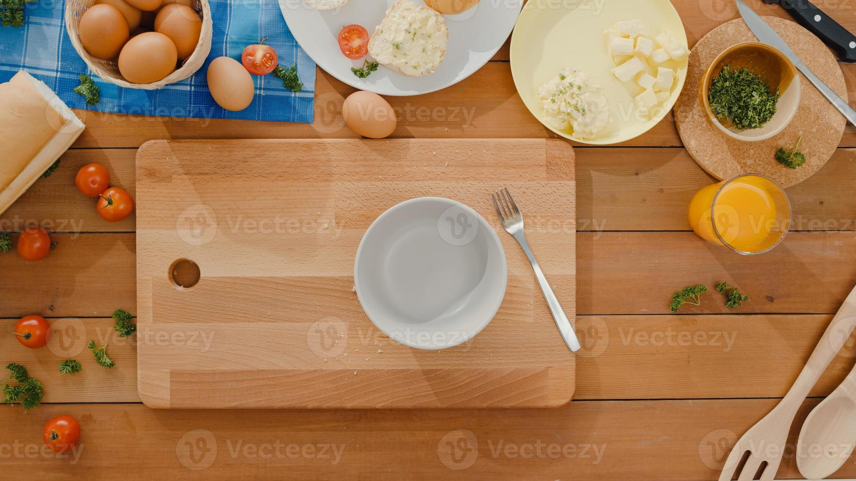Hands of young Asian woman chef crack egg into ceramic bowl cook omelette with vegetables on wooden board on kitchen table in home. Lifestyle healthy eat and traditional bakery concept. Top view shot. photo