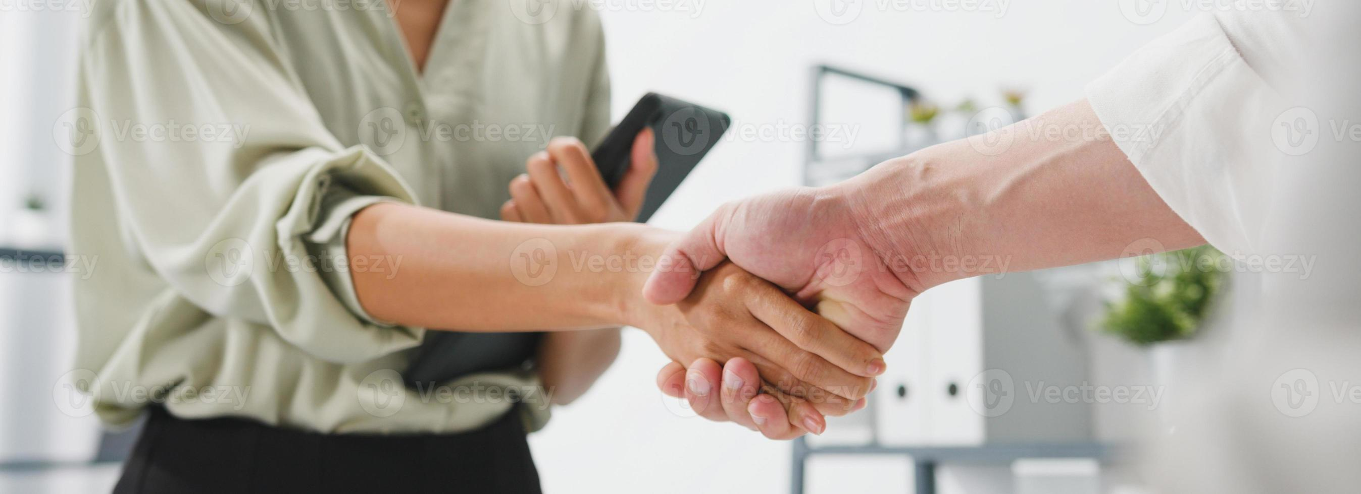 Young creative people in smart casual wear discussing business shaking hands together in office. Partner cooperation, coworker teamwork concept. Panoramic banner background with copy space. photo