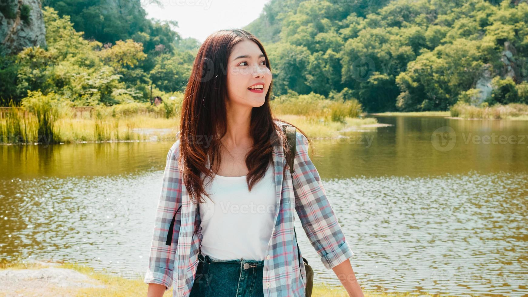 Cheerful young traveler Asian lady with backpack walking at the mountain lake. Korean teen girl enjoy her holidays adventure feeling happy freedom. Lifestyle travel and relax in free time concept. photo