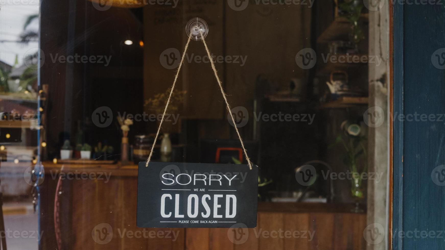Sorry we're closed vintage black and white retro sign on a coffee glass door cafe after coronavirus lockdown quarantine. Owner small business, food and drink, business financial crisis concept. photo