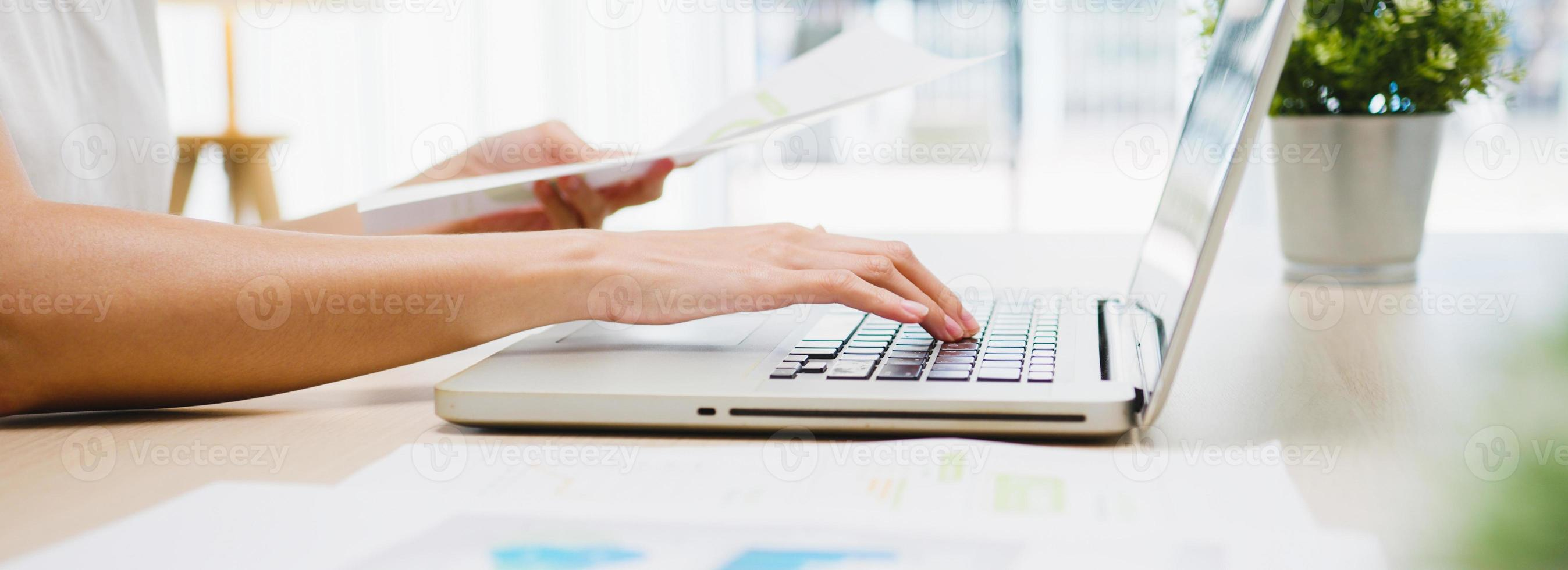 Freelance Asia businesswoman casual wear using laptop working in living room at home. Remotely, social distancing, quarantine for corona virus prevention. Panoramic banner background with copy space. photo