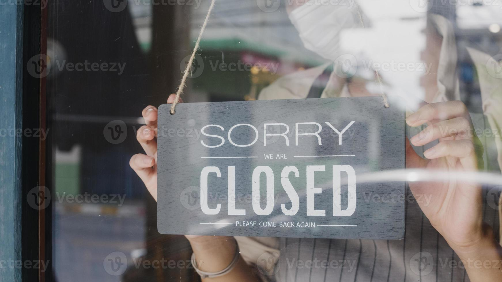 Young Asia girl wear face mask turning a sign from open to closed sign on glass door cafe after coronavirus lockdown quarantine. Owner small business, food and drink, business financial crisis concept photo