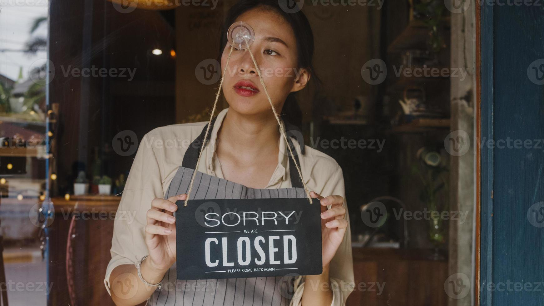 Young Asia manager girl turning a sign from open to closed sign on glass door cafe after coronavirus lockdown quarantine. Owner small business, food and drink, business financial crisis concept. photo