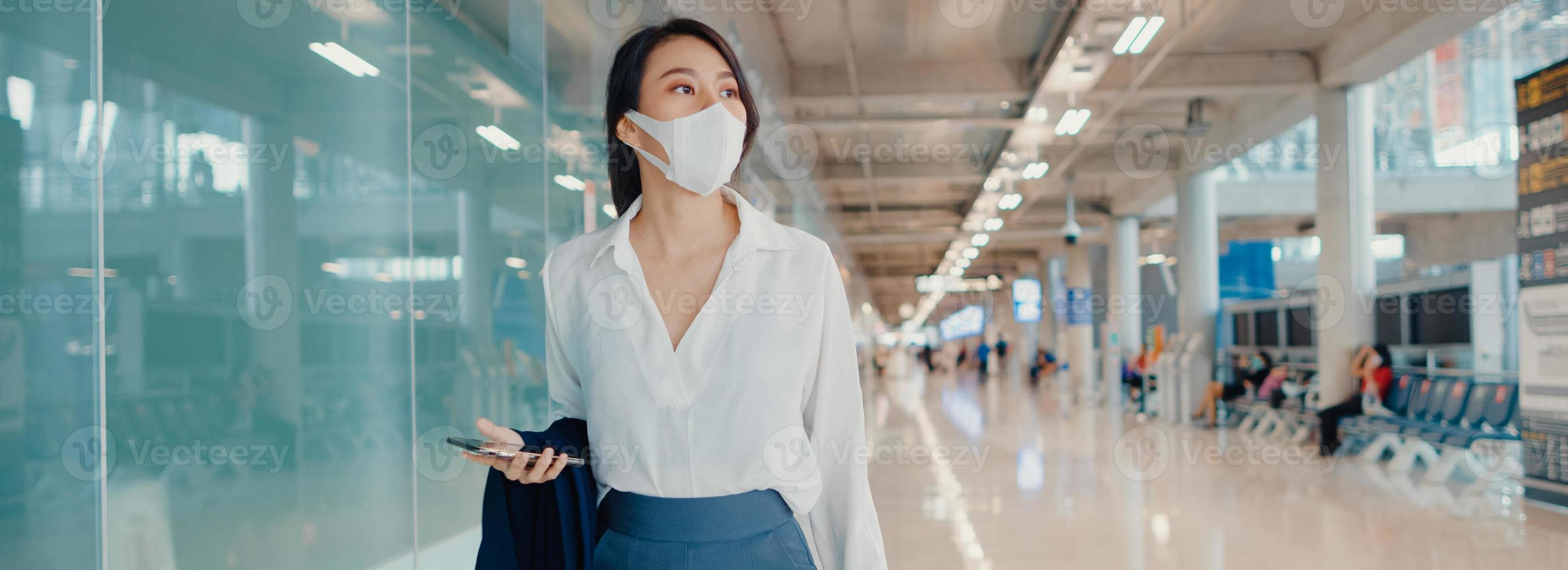 Asian business girl use smart phone for check in boarding pass walk with luggage to terminal domestic flight at airport. Business commuter covid pandemic, panoramic banner background with copy space. photo