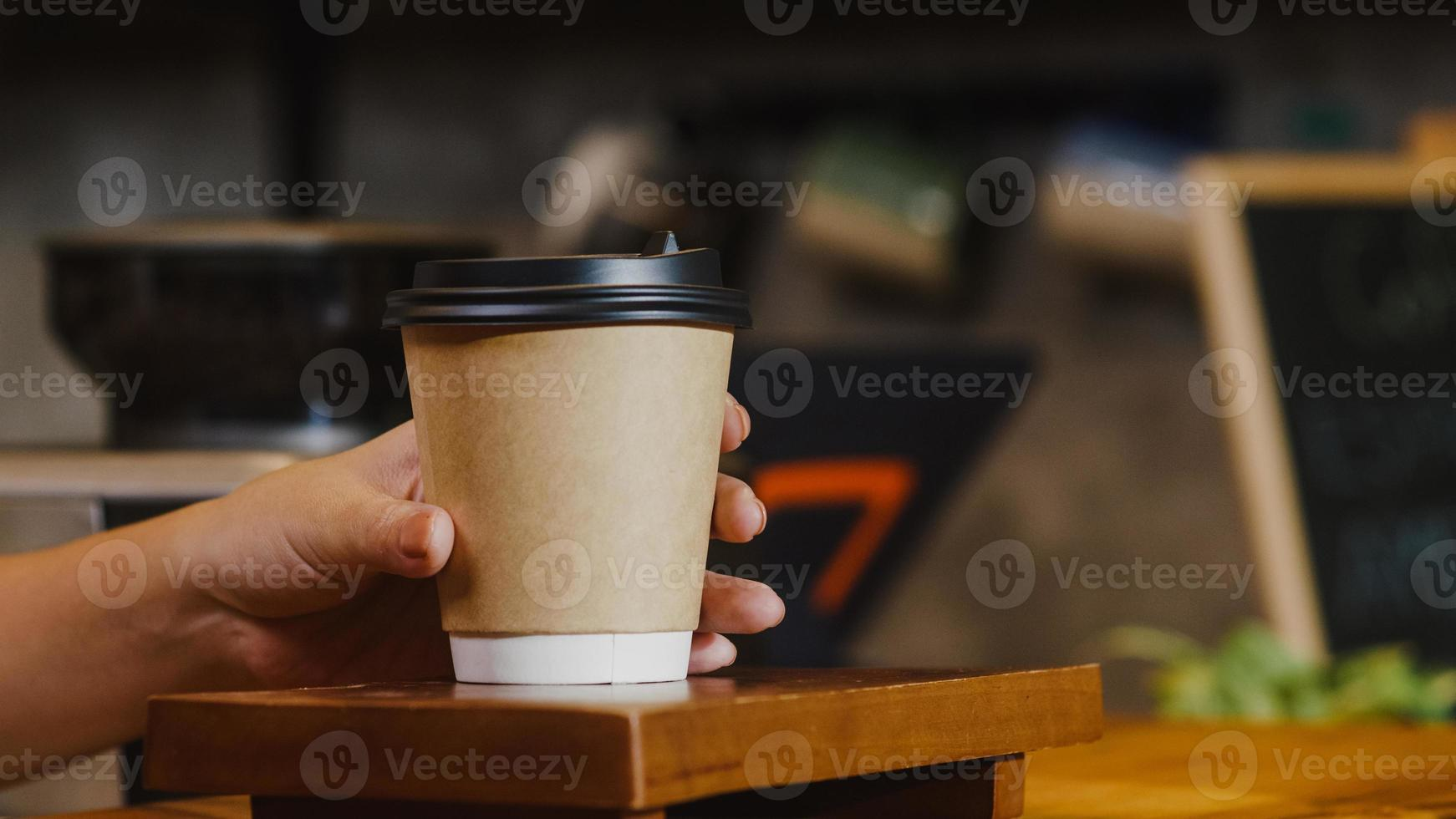 Young Asia female barista serving take away hot coffee paper cup to consumer standing behind bar counter at cafe restaurant. Owner small business, food and drink, service mind concept. photo