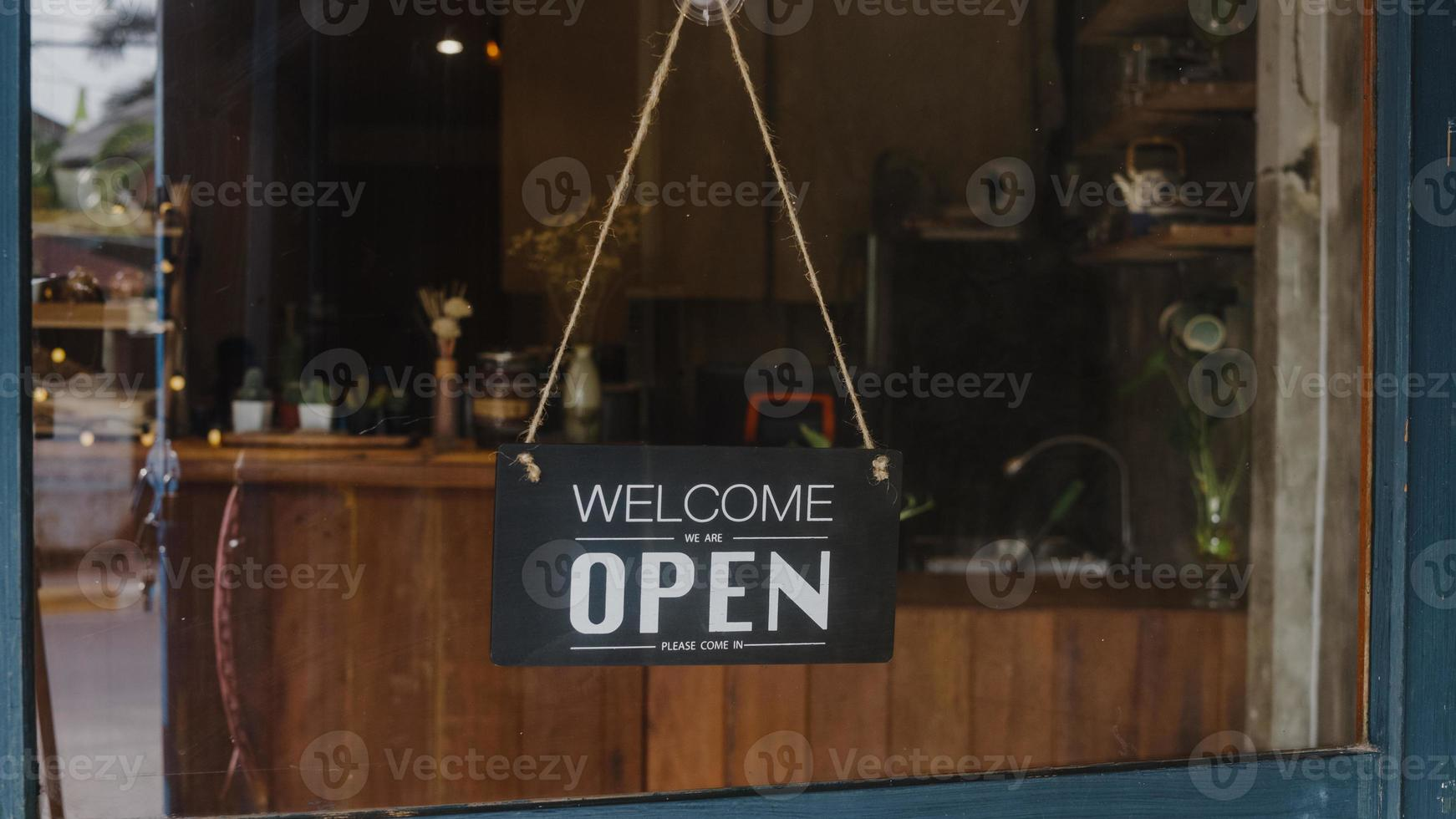 Welcome we're open vintage black and white retro sign on a coffee glass door cafe after coronavirus lockdown quarantine. Owner small business, food and drink, business reopen again concept. photo