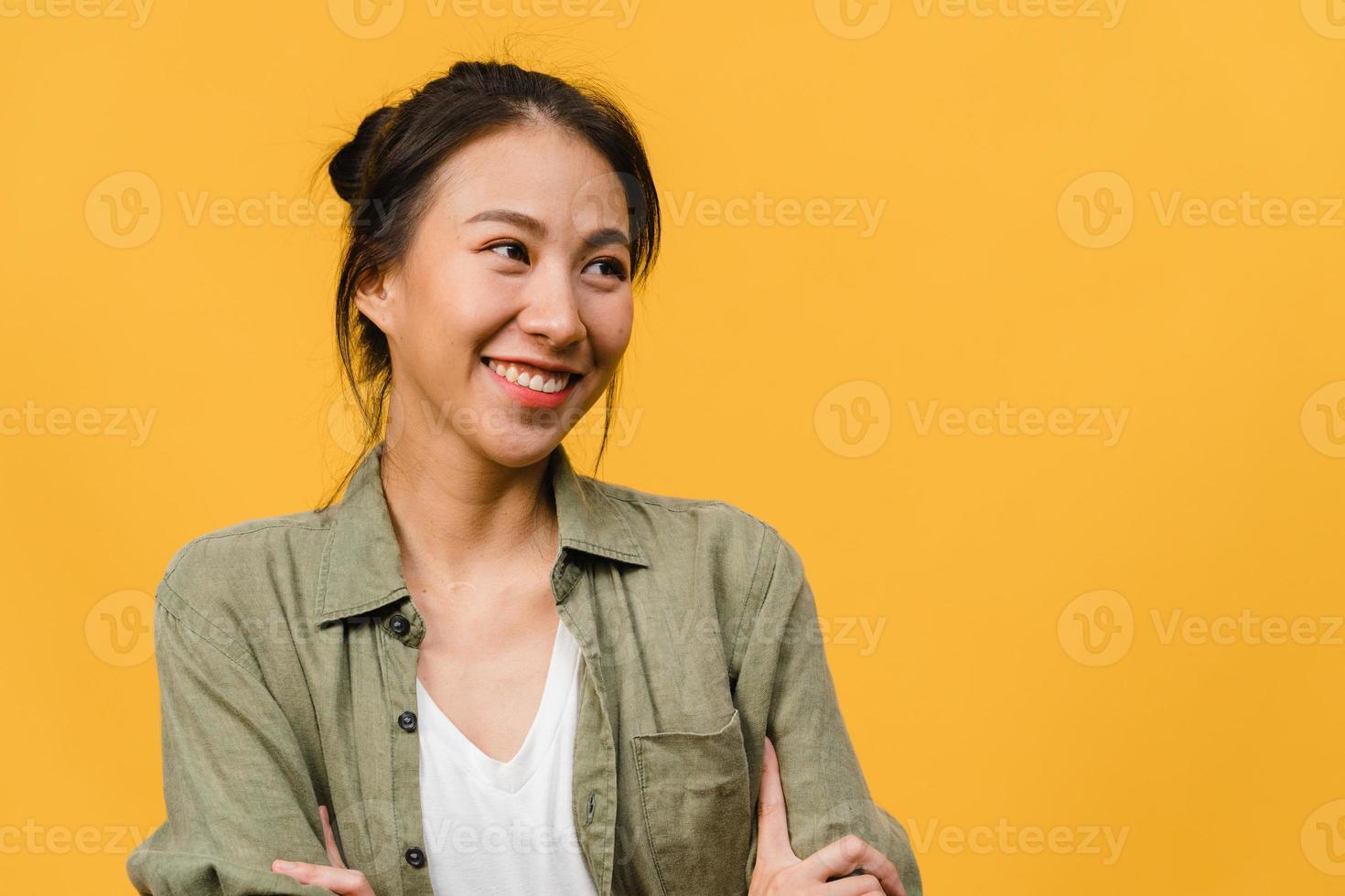 Retrato de joven asiática con expresión positiva, brazos cruzados, sonrisa amplia, vestida con ropa informal sobre fondo amarillo. feliz adorable mujer alegre se regocija con el éxito. concepto de expresión facial. foto