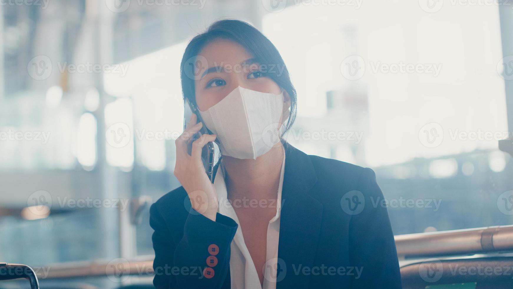 traje de desgaste de la muchacha de negocios asiática inteligente sentado con la maleta en el banco llamada teléfono inteligente hablar con el socio esperar el vuelo en el aeropuerto. viajero de viajes de negocios en la pandemia de covid, concepto de viajes de negocios. foto