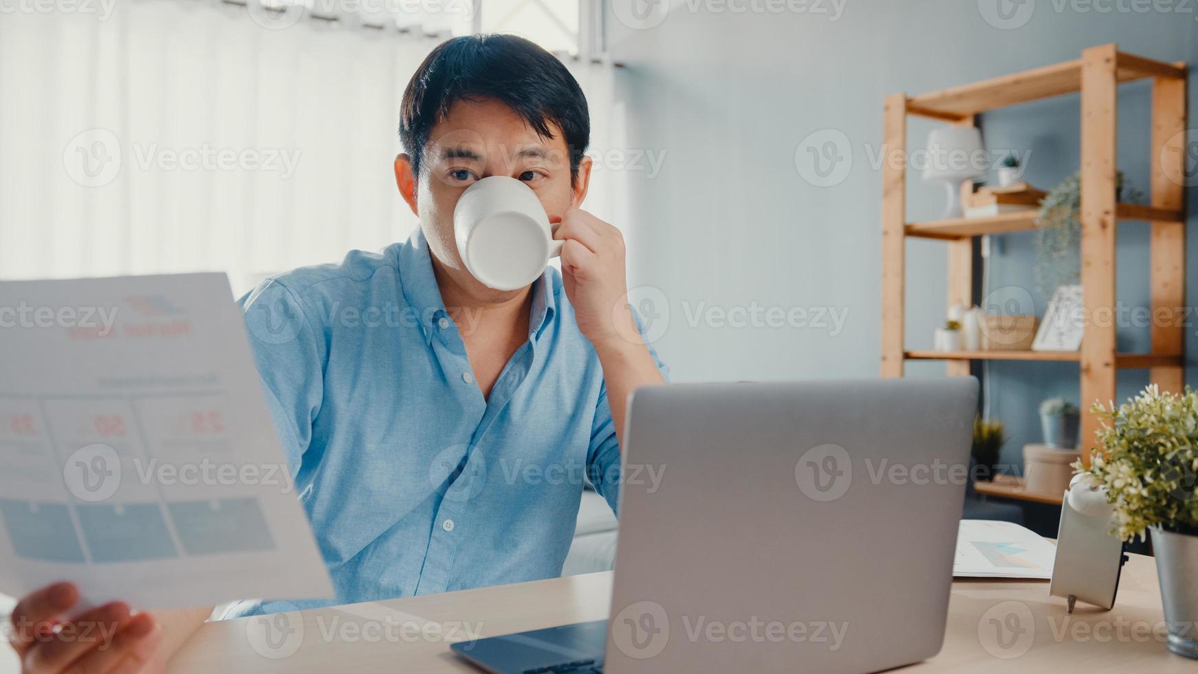 freelance asia guy casual wear usando laptop y tomando café en la sala de estar en casa. trabajo desde casa, trabajo a distancia, educación a distancia, distanciamiento social, cuarentena para la prevención del coronavirus. foto