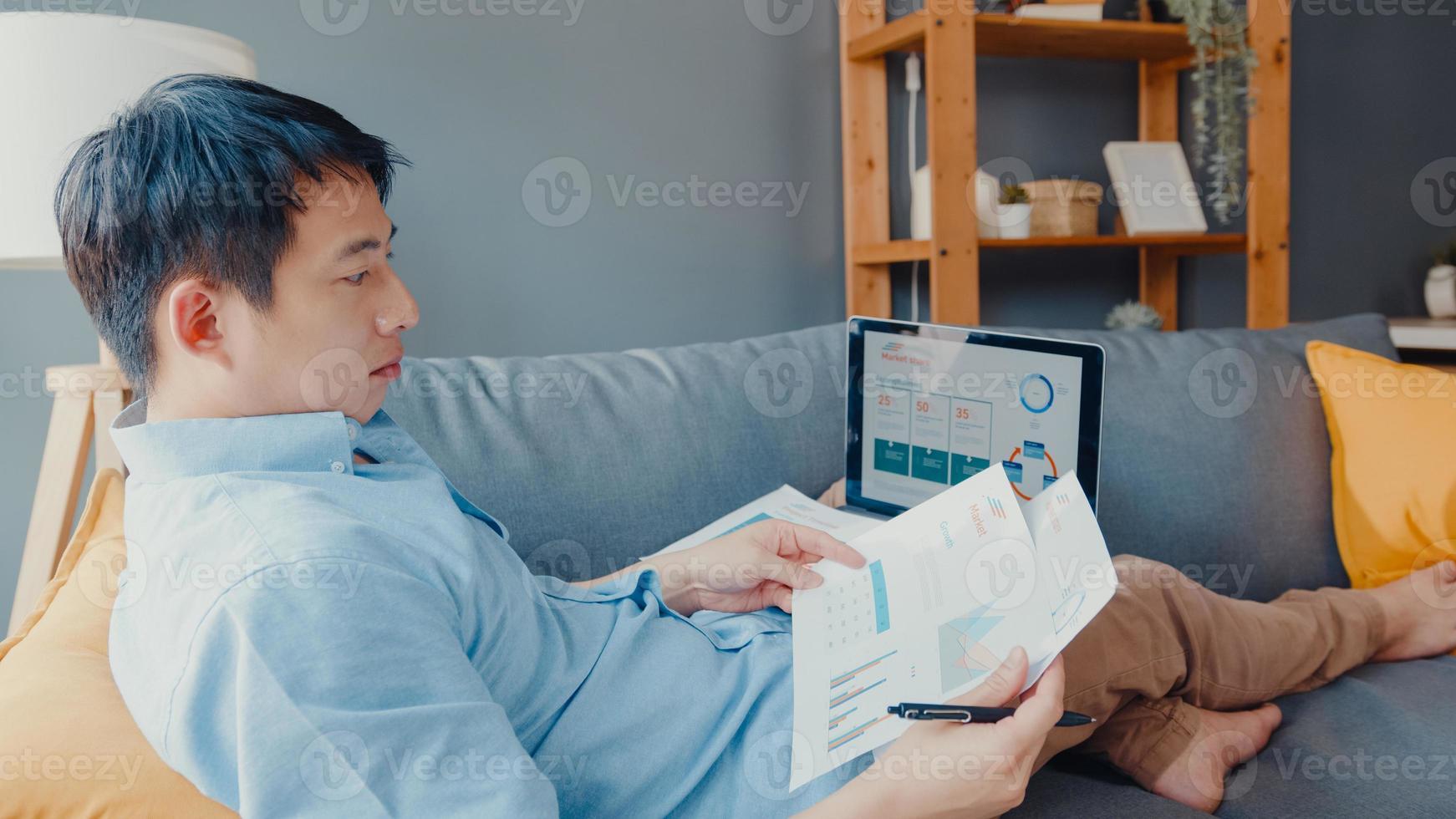 ropa casual de chico asiático independiente con aprendizaje en línea portátil en la sala de estar de la casa. trabajo desde casa, trabajo a distancia, educación a distancia, distanciamiento social, cuarentena para la prevención del coronavirus. foto