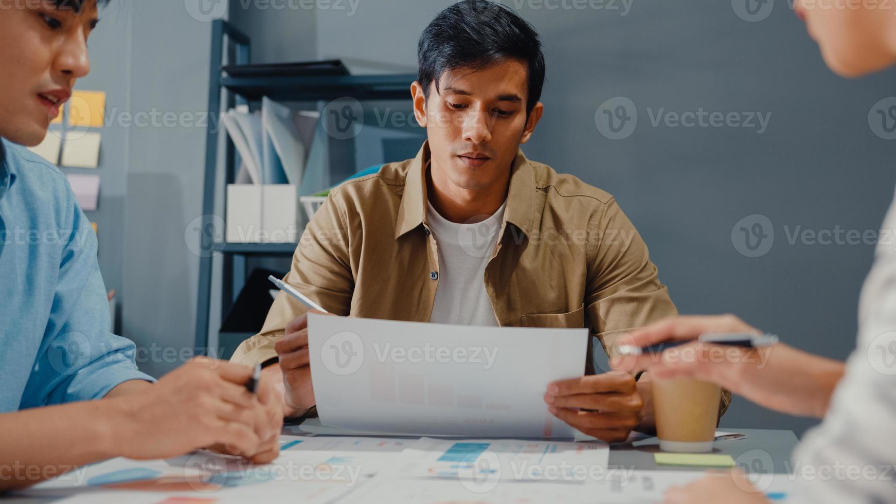 felices jóvenes empresarios asiáticos y mujeres de negocios reunidos intercambiando ideas sobre nuevas ideas sobre proyectos para su socio trabajando juntos planificando la estrategia de éxito disfrutan del trabajo en equipo en la pequeña y moderna oficina en casa. foto