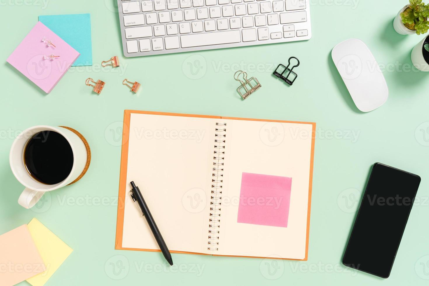 Foto creativa plana del escritorio del espacio de trabajo. escritorio de oficina de vista superior con teclado, mouse y cuaderno negro de maqueta abierta sobre fondo de color verde pastel. vista superior maqueta con fotografía de espacio de copia.