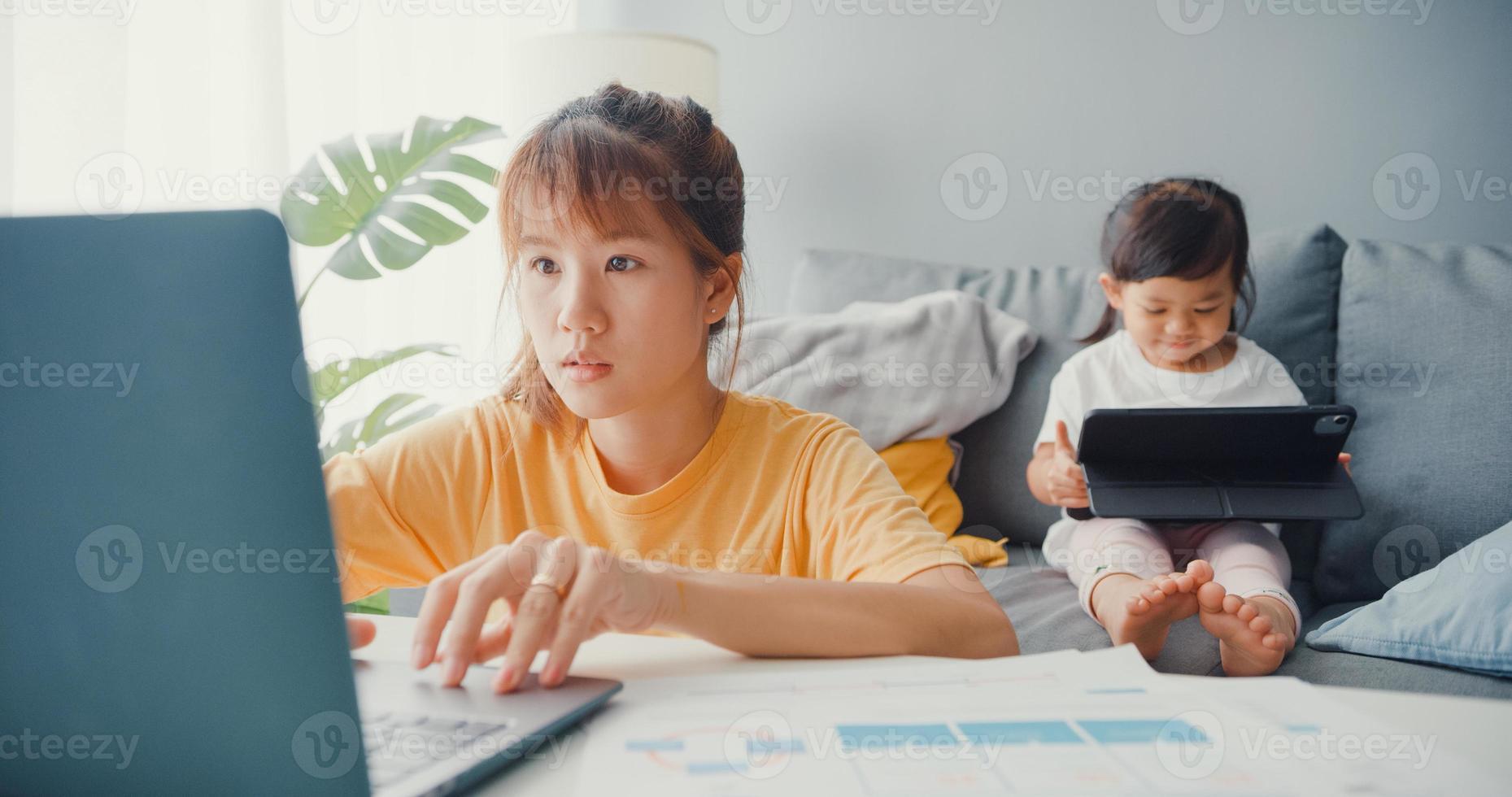 Feliz madre de familia de Asia alegre usando la computadora portátil con su hijo mantenga la caricatura de interés de la tableta en el sofá mientras trabaja desde la casa en la sala de estar. distanciamiento social, cuarentena para la prevención del coronavirus. foto