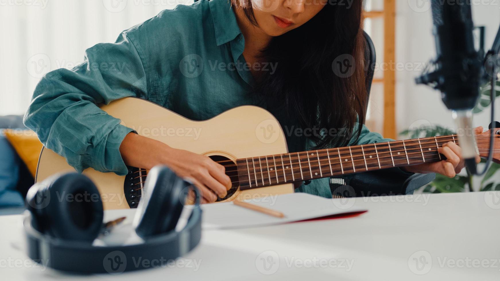 feliz mujer asiática compositora tocar la guitarra acústica escuchar la canción desde el teléfono inteligente pensar y escribir notas letras de canciones en papel sentarse en la sala de estar en casa estudio. producción musical en el concepto de casa. foto