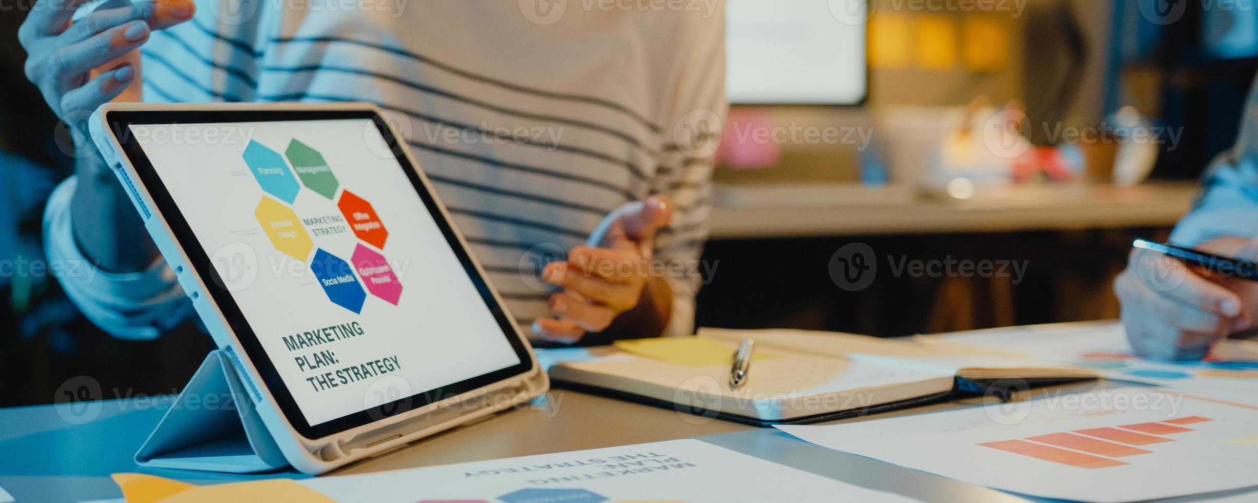 Reunión de empresarios de Asia, análisis de estadísticas, lluvia de ideas y encabezado del gráfico de tableta de retención de equipo y el empleado toma nota en la noche de la oficina en casa. Fondo de banner panorámico con espacio de copia. foto