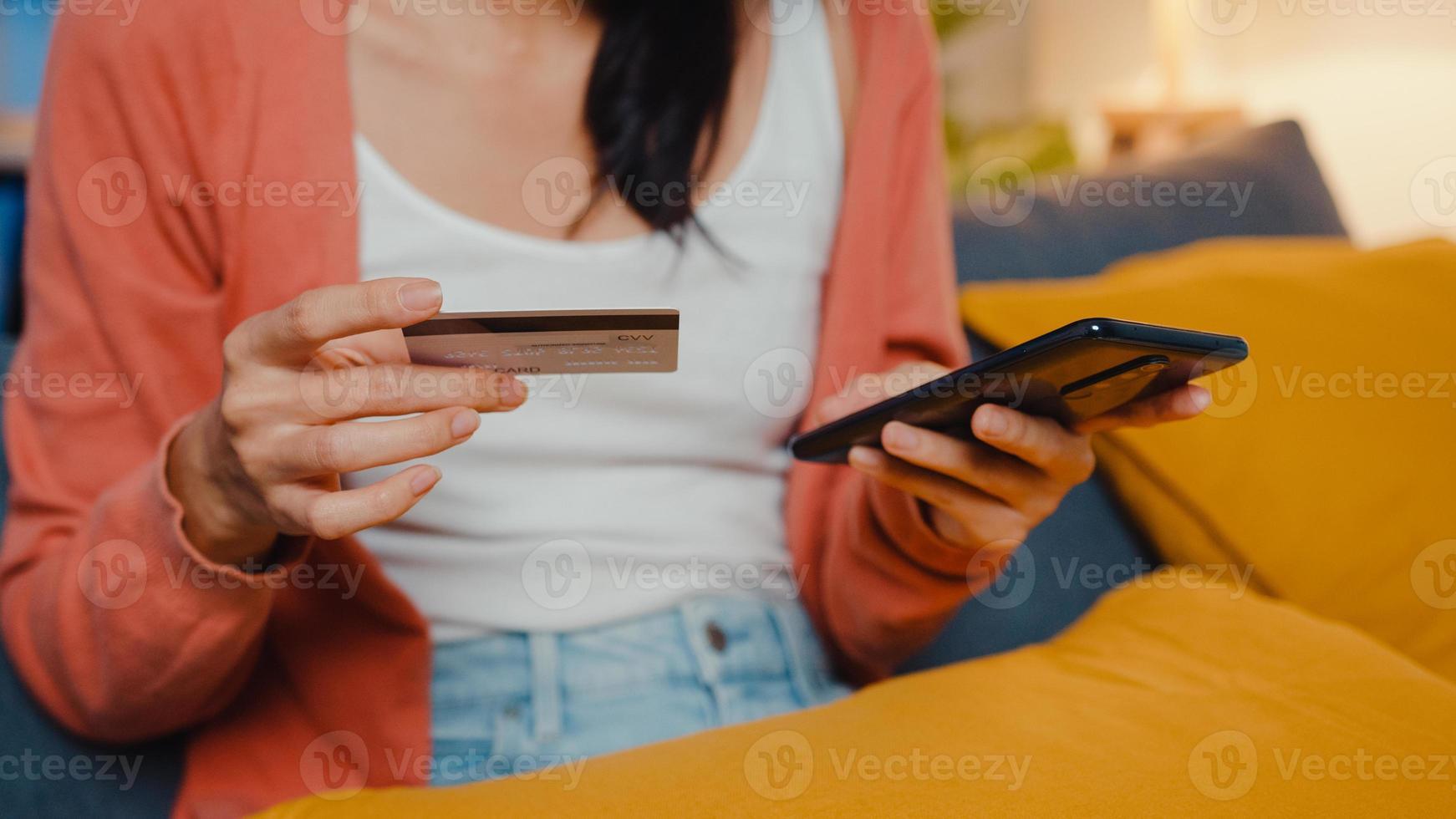 la noche hermosa dama asiática sonriente usa el teléfono celular para ordenar productos de compras en línea con tarjeta de crédito en el sofá de la sala de estar. quedarse en casa, actividad de auto cuarentena, actividad divertida para la cuarentena de covid. foto