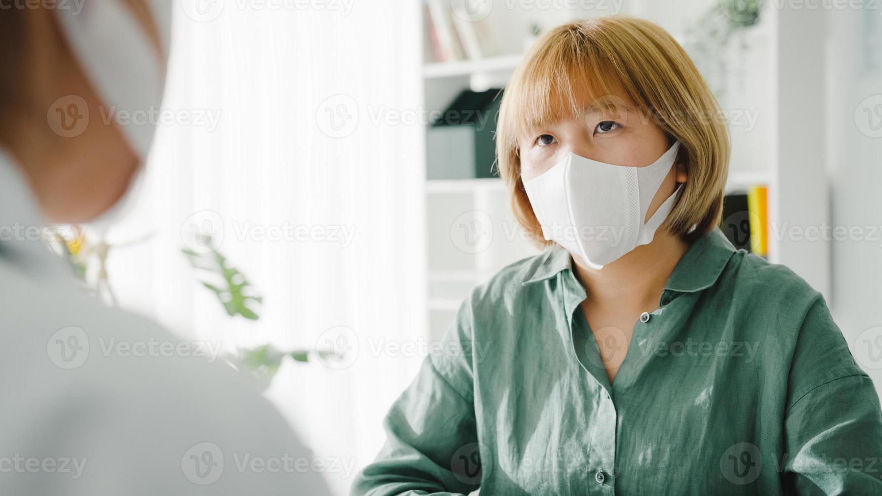 La joven doctora de Asia usa una máscara protectora usando el portapapeles está brindando una gran charla de noticias sobre los resultados o los síntomas con la paciente en la oficina del hospital. estilo de vida nuevo normal después del virus corona. foto