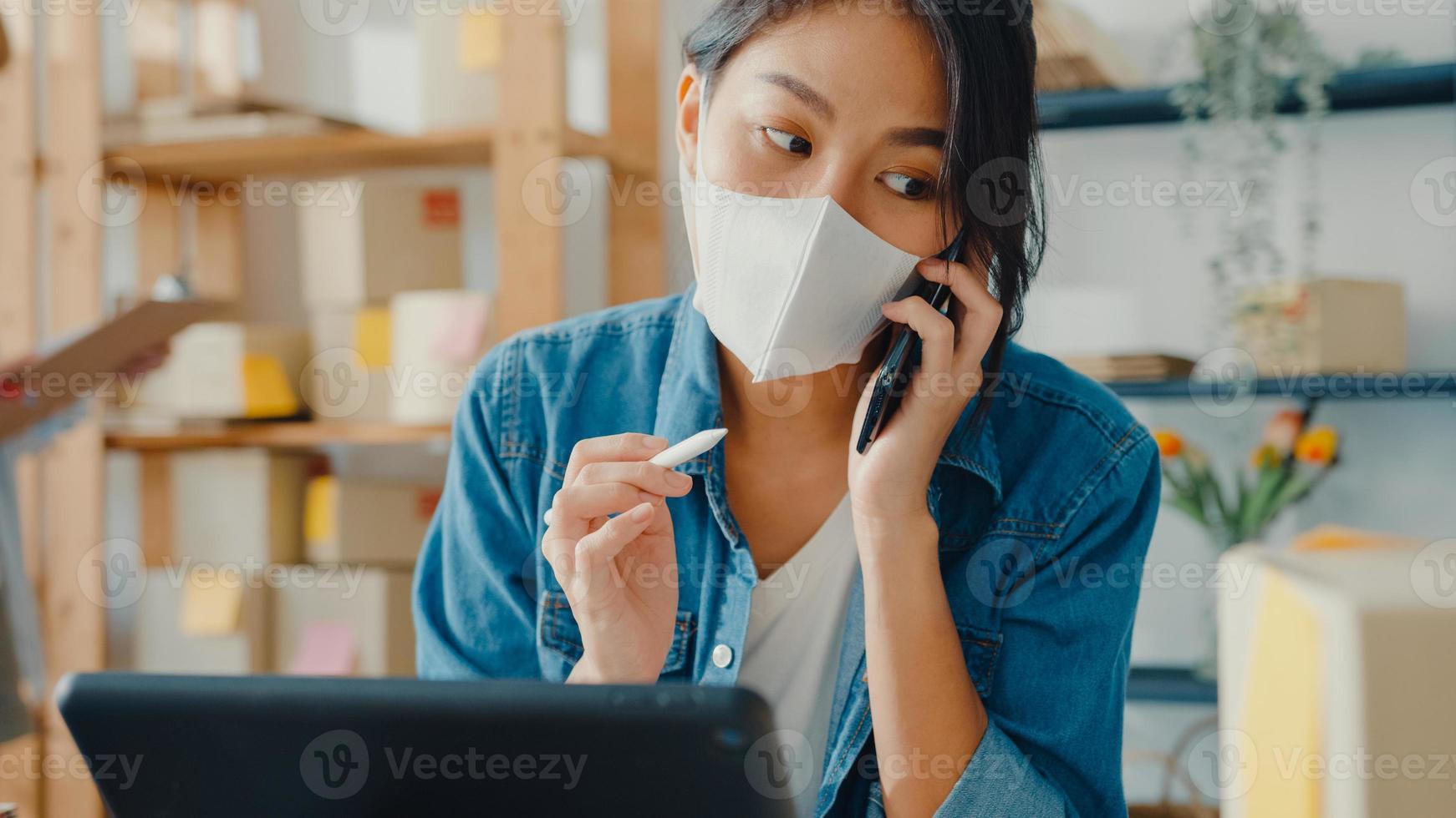Jóvenes empresarias asiáticas usan mascarilla usando una llamada de teléfono móvil, reciben una orden de compra y verifican el producto en el trabajo de stock en la oficina en casa. propietario de una pequeña empresa, concepto independiente de entrega de mercado en línea. foto