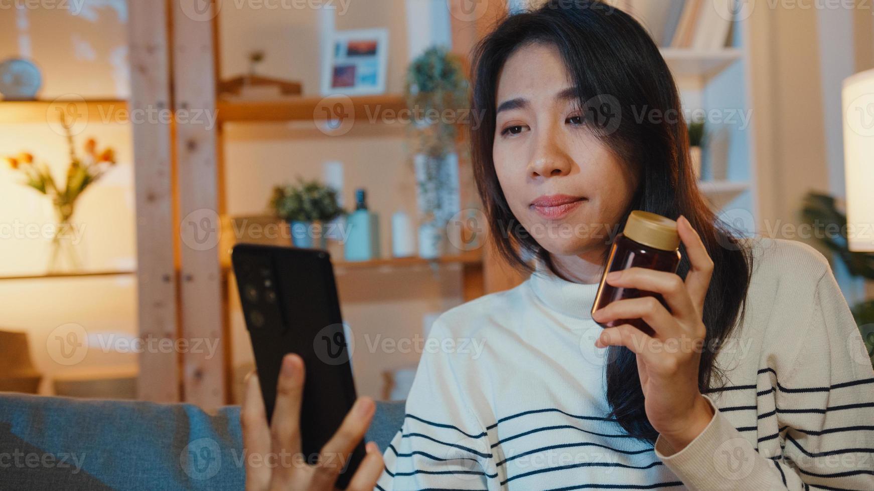 enferma joven asiática mantenga la medicina sentarse en el sofá videollamada con el teléfono consulte con el médico en la noche en casa. chica toma medicamentos después de la orden del médico, cuarentena en la casa, virus corona de distancia social. foto