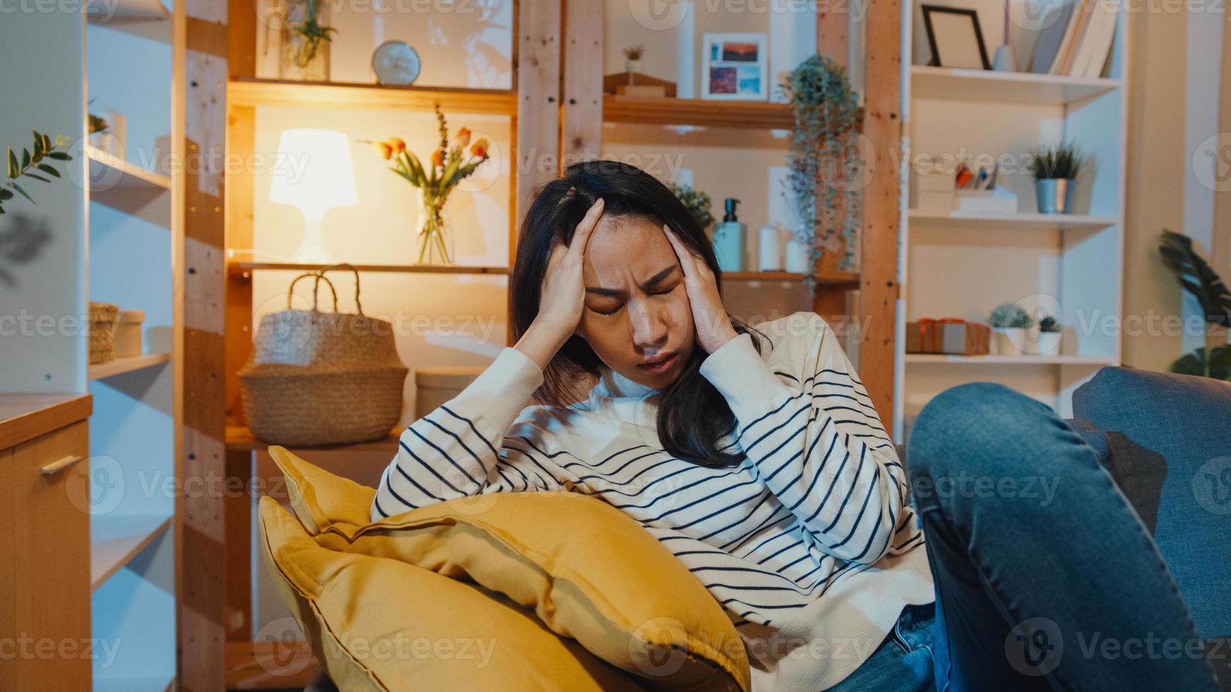 pensativa dama de asia que sufre de insomnio se sienta en el sofá en la sala de estar en la noche de la casa con un adolescente deprimido y triste que se siente solo, pasa tiempo solo en casa, distancia social, cuarentena de coronavirus. foto