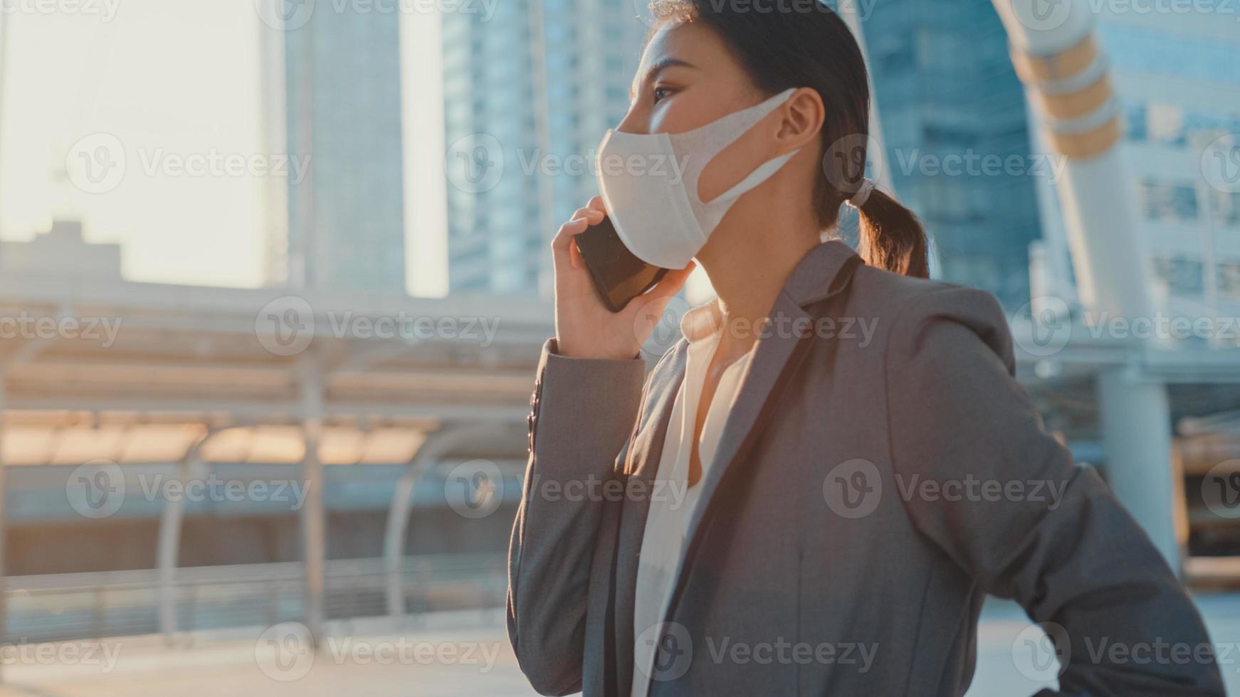 joven empresaria de asia en la oficina de moda vestir usar mascarilla médica hablar por teléfono mientras camina sola al aire libre en la ciudad urbana. negocio en marcha, distanciamiento social para evitar la propagación del concepto covid-19. foto