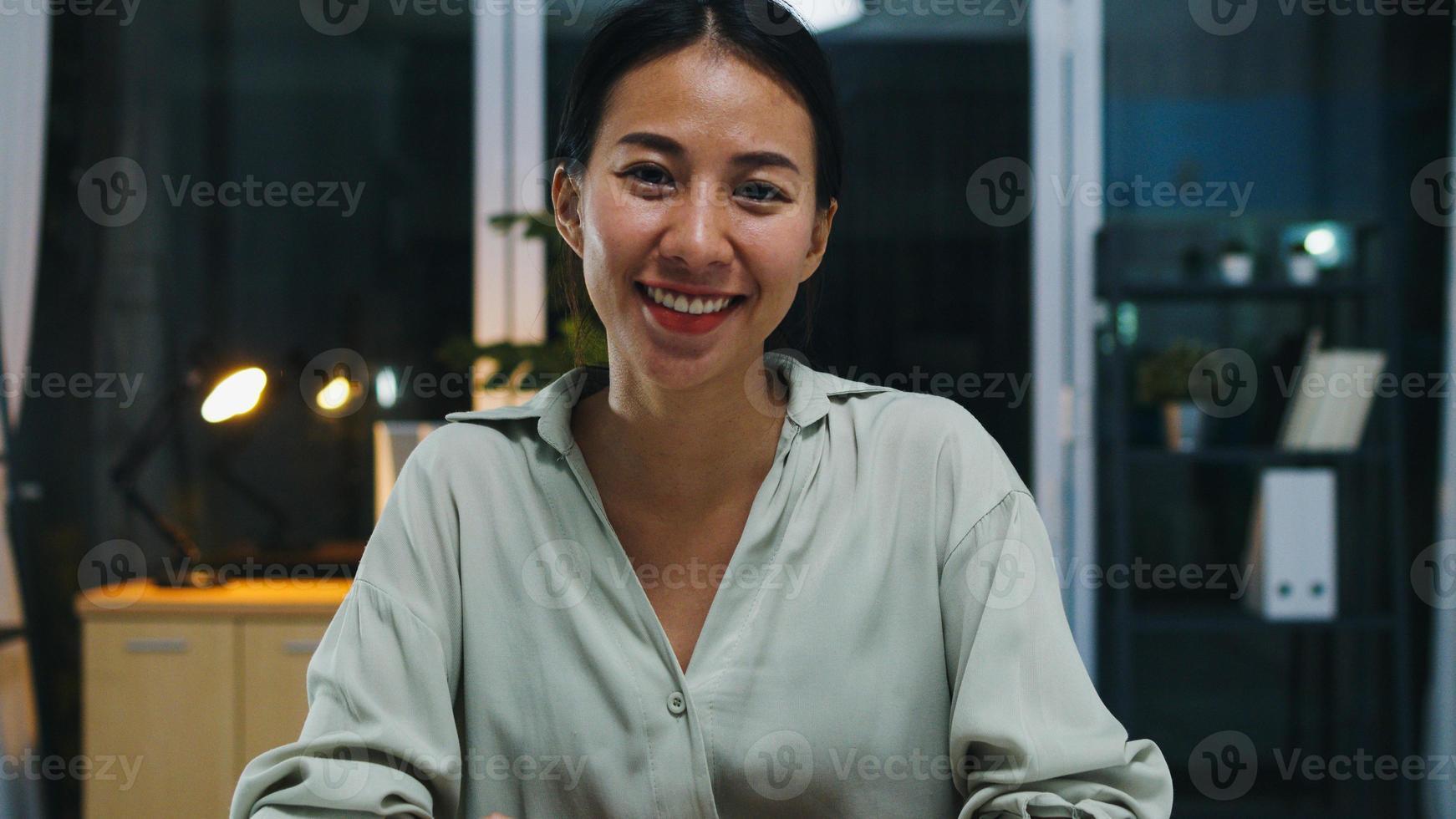 Retrato de hermosa mujer de negocios ejecutiva elegante ropa casual mirando a cámara y sonriendo, feliz en la noche de trabajo de oficina moderna. jovencita asiática habla con un colega en una reunión de videollamada en casa. foto
