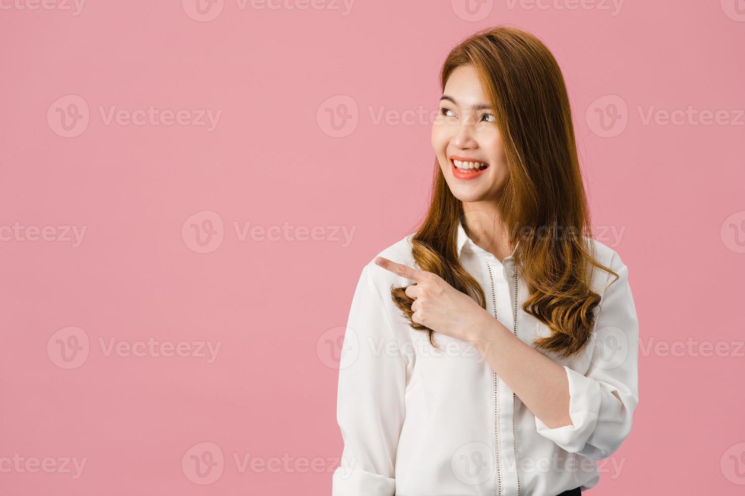 Retrato de joven asiática sonriendo con expresión alegre, muestra algo sorprendente en el espacio en blanco en ropa casual y de pie aislado sobre fondo rosa. concepto de expresión facial. foto