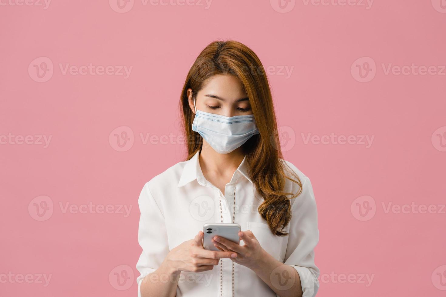 Joven asiática con mascarilla médica mediante teléfono móvil vestida con ropa casual aislada sobre fondo rosa. autoaislamiento, distanciamiento social, cuarentena para la prevención del coronavirus. foto