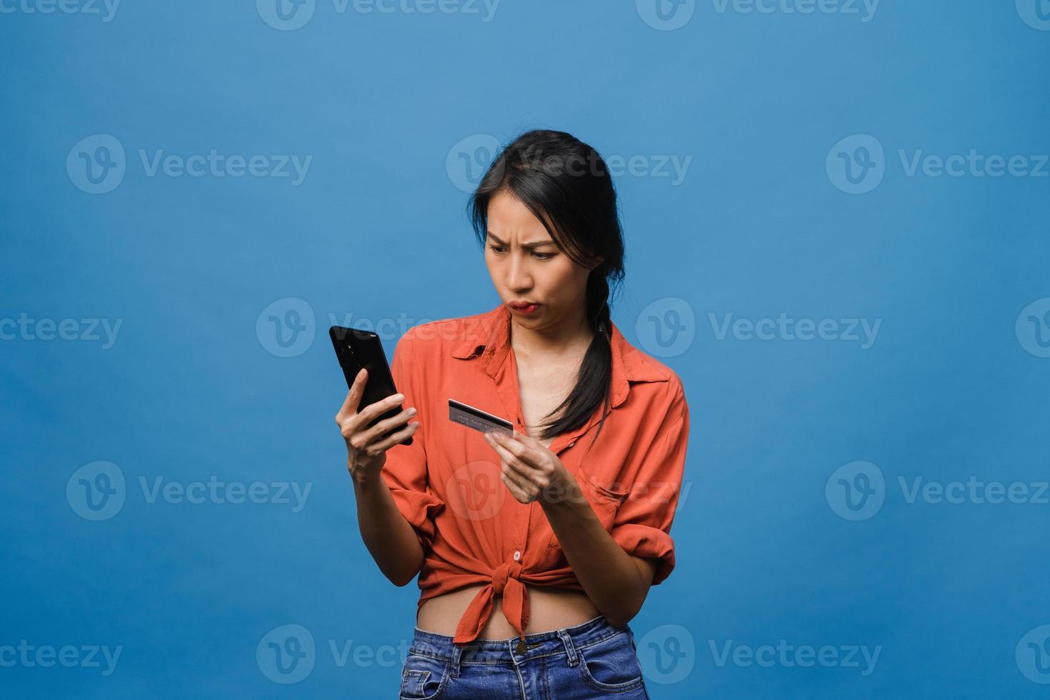 Jovencita asiática usando teléfono y tarjeta bancaria de crédito con expresión negativa, gritos emocionados, gritos emocionales enojados en ropa casual y de pie aislado sobre fondo azul. concepto de expresión facial. foto
