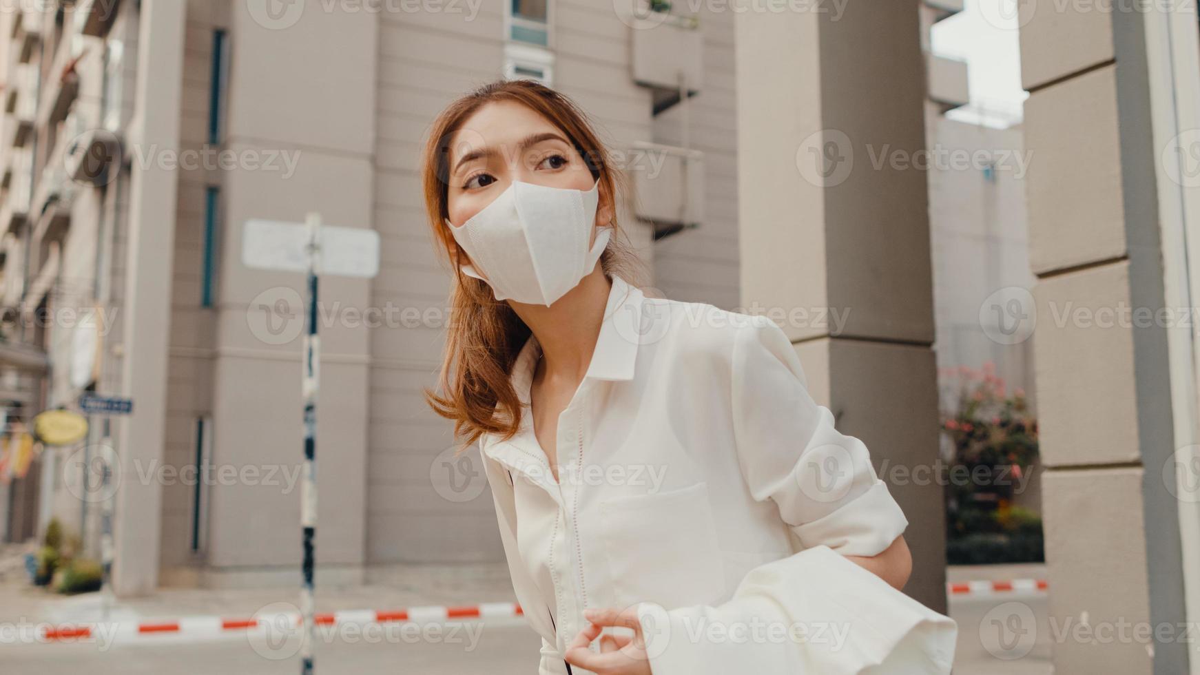 Exitosa empresaria asiática joven en ropa de oficina de moda usa mascarilla médica caminando sola al aire libre en la ciudad moderna urbana en la mañana. pandemia de brote de covid-19, concepto de negocio en movimiento. foto