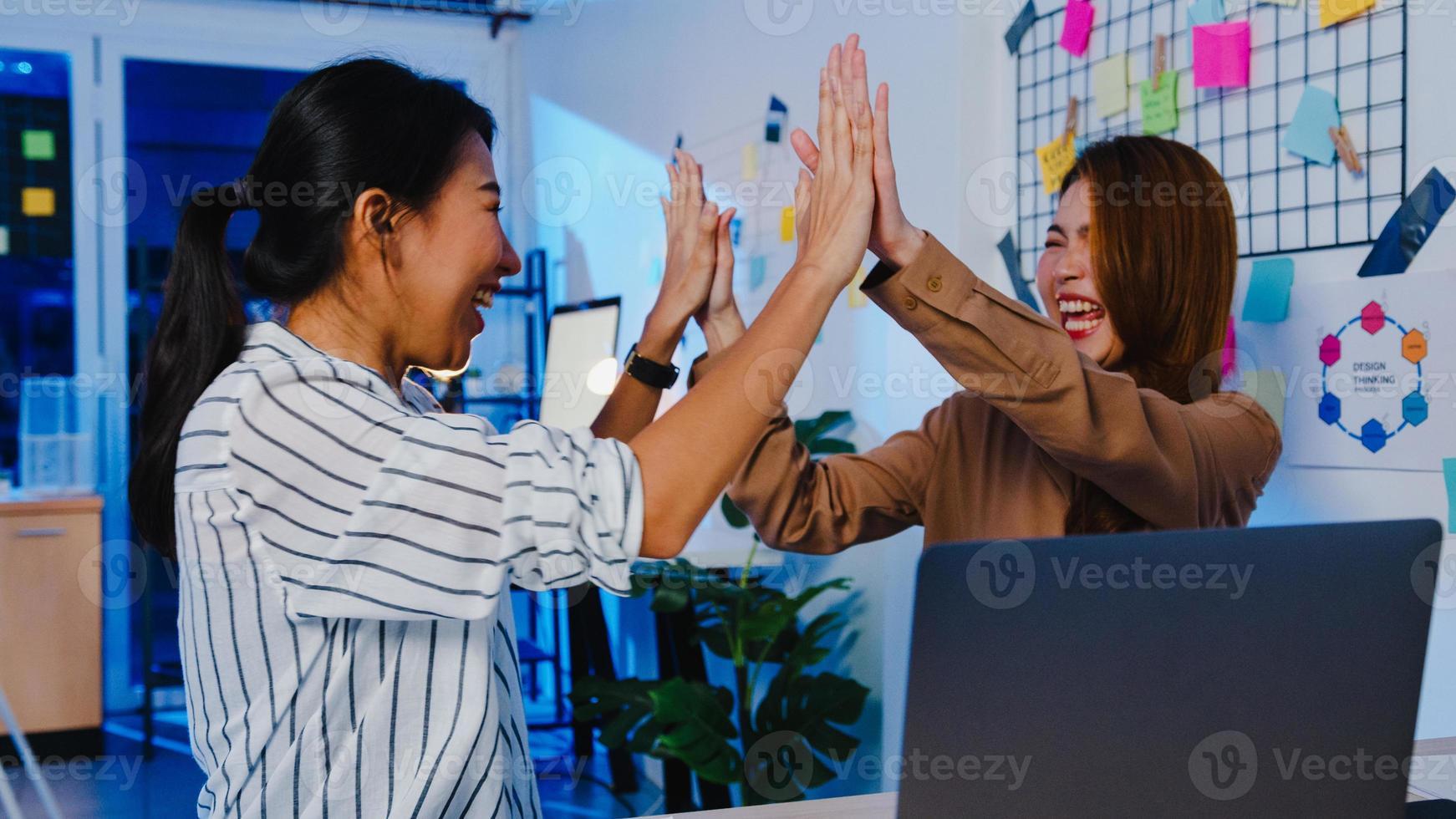 grupo de empresaria de asia en casual discutiendo negocios celebran dando cinco después de tratar sintiéndose feliz y firmando contrato o acuerdo en la oficina en casa de noche. compañero de trabajo poner en marcha el concepto de trabajo en equipo. foto