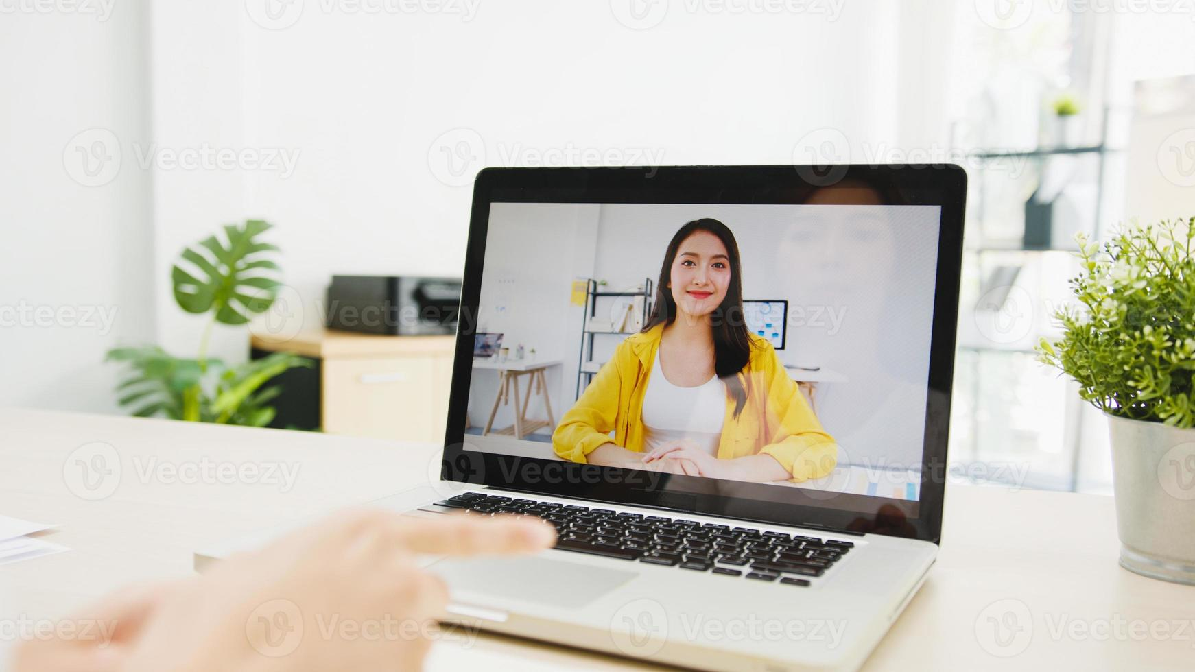 Asia empresaria usando una computadora portátil hable con sus colegas sobre el plan en una reunión de videollamada mientras trabaja desde su casa en la sala de estar. autoaislamiento, distanciamiento social, cuarentena para la prevención del coronavirus. foto